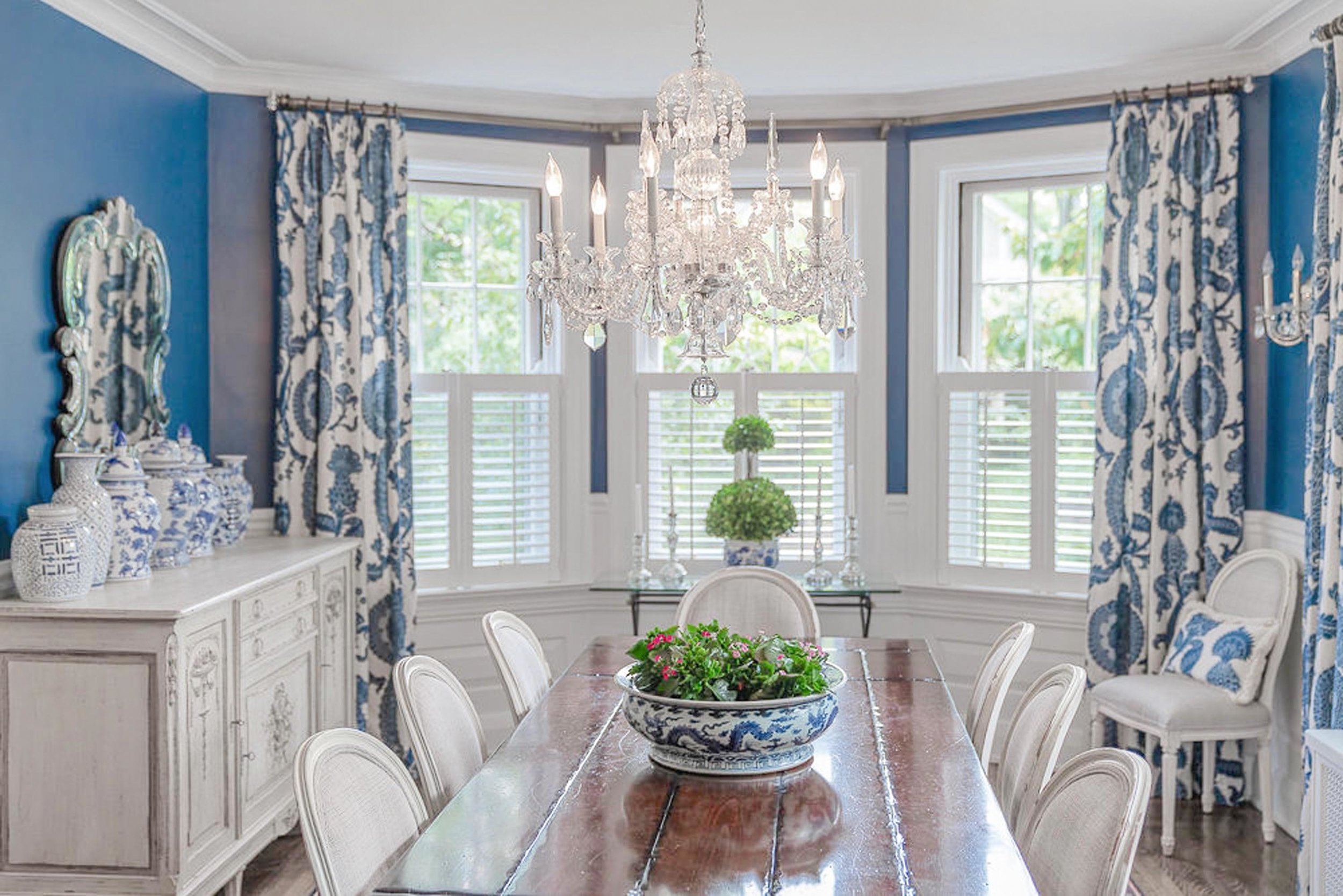 Dining room with wooden table, white chairs and crystal chandelier