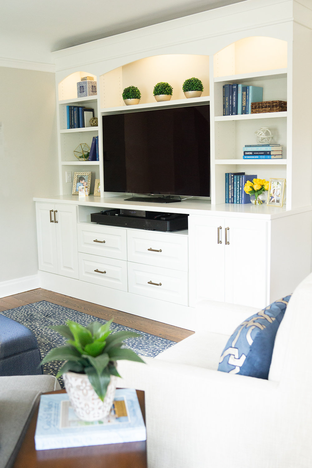 Modern living room with smart TV on white wooden cabinet with books and plants