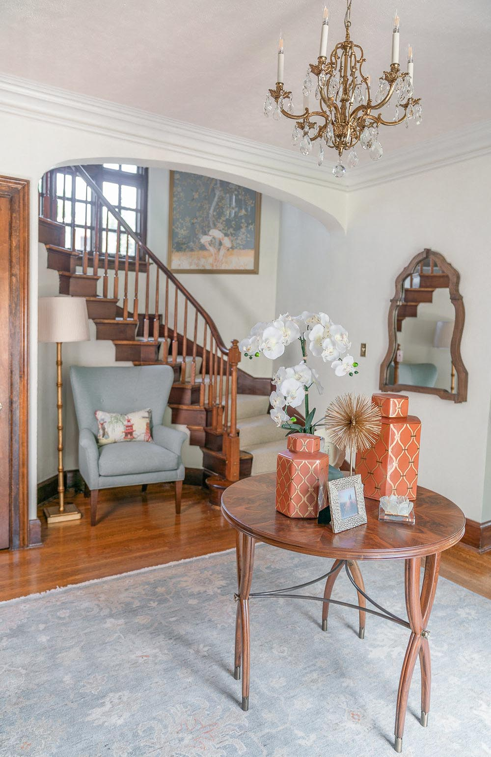 Living room with round table, chandelier and stair