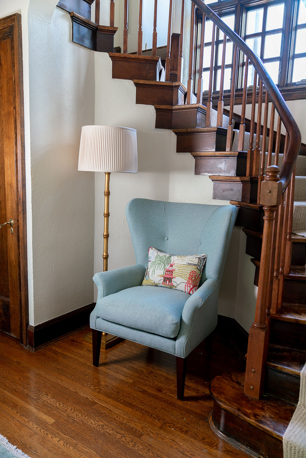 Wooden stairway with armchair and floor lamp