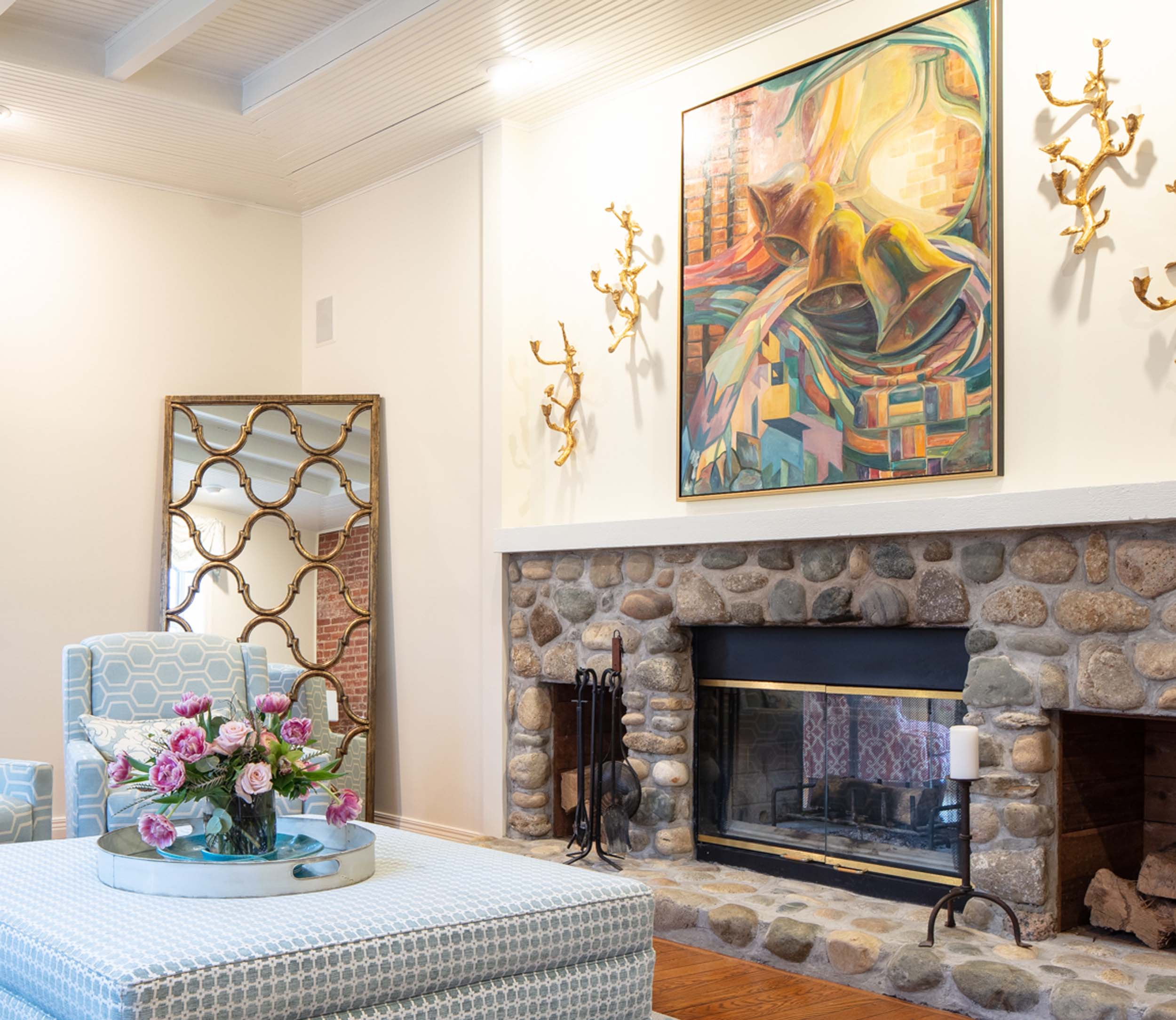 Living room with stone fireplace, ottoman and artwork on the wall