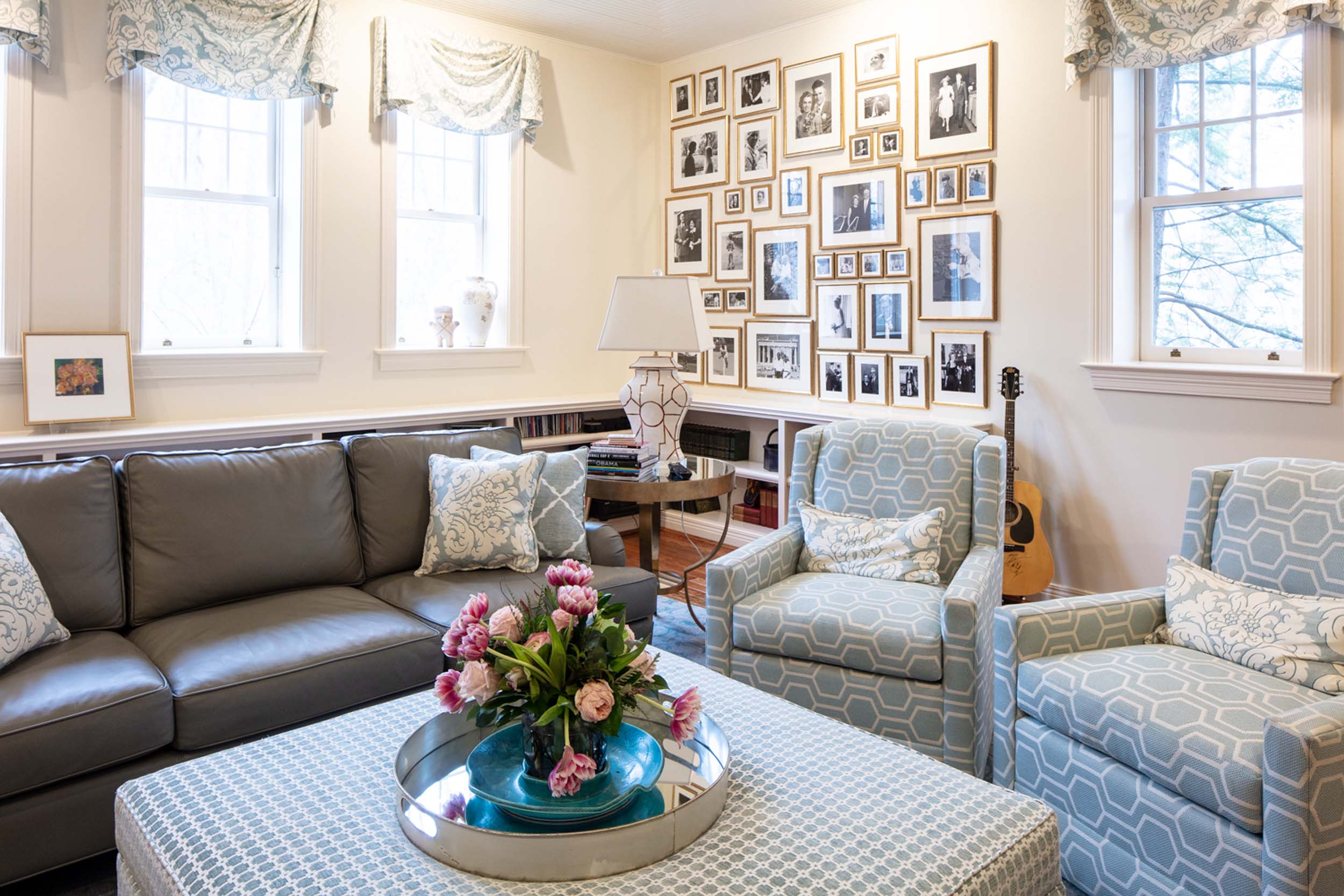 Living room with sofa, ottoman and a flowers and picture frames on the wall