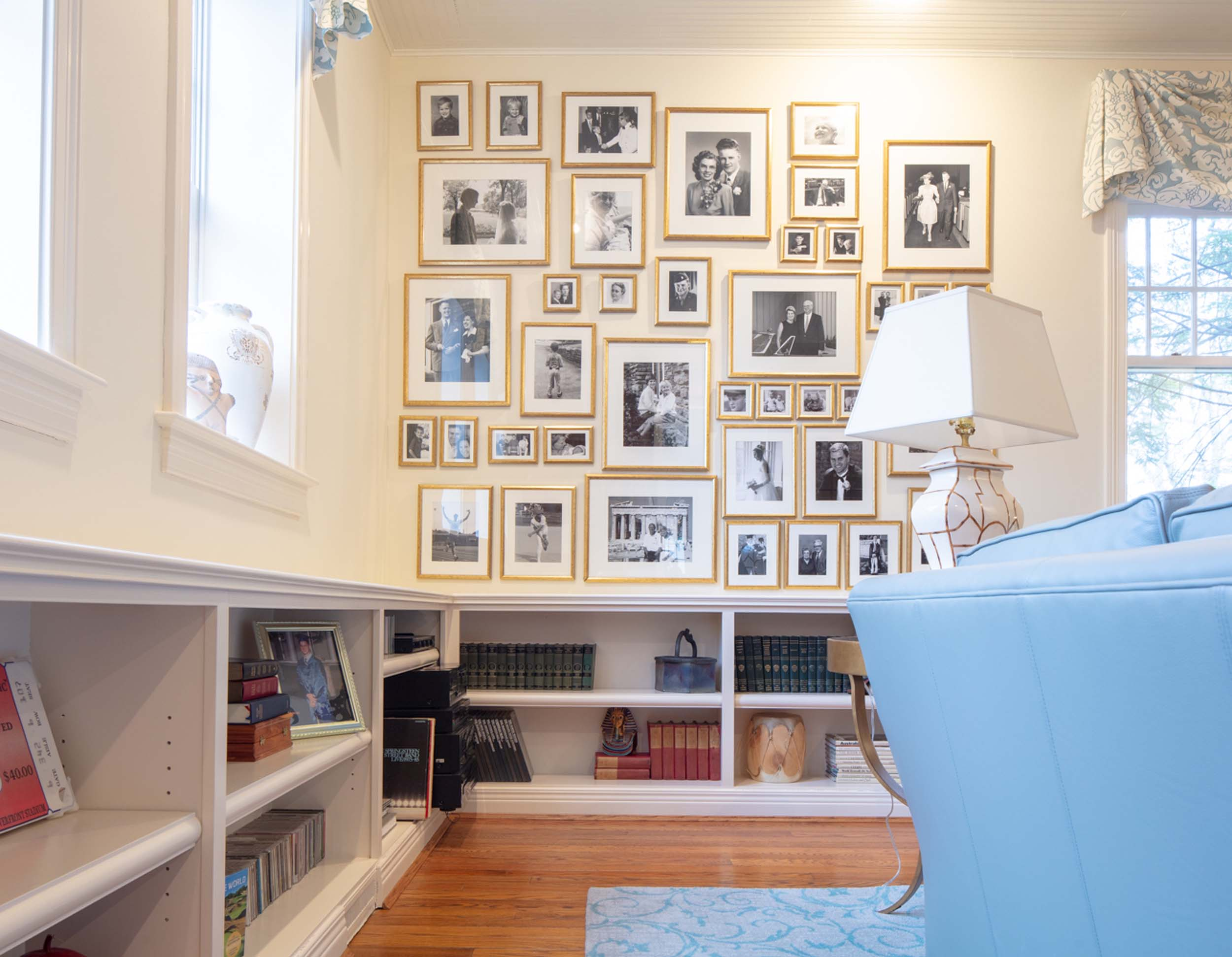 Living room with white wooden bookshelf and picture frames on the wall