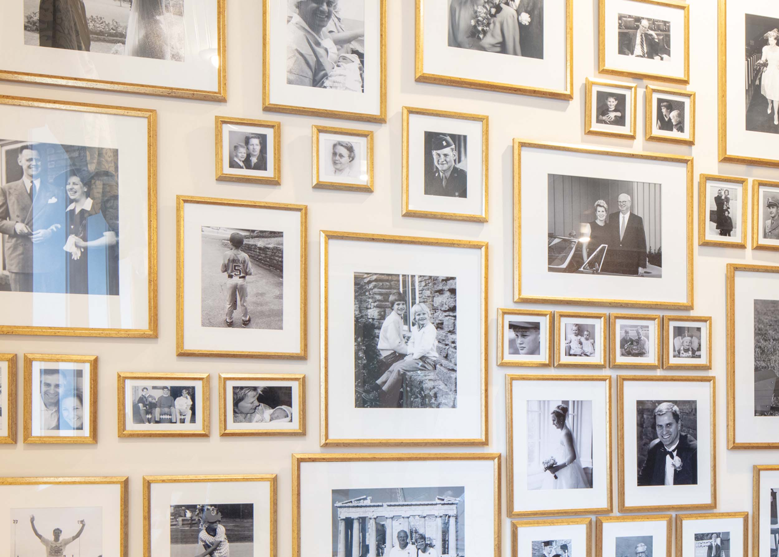 A wall with photos of the family in various photo frames