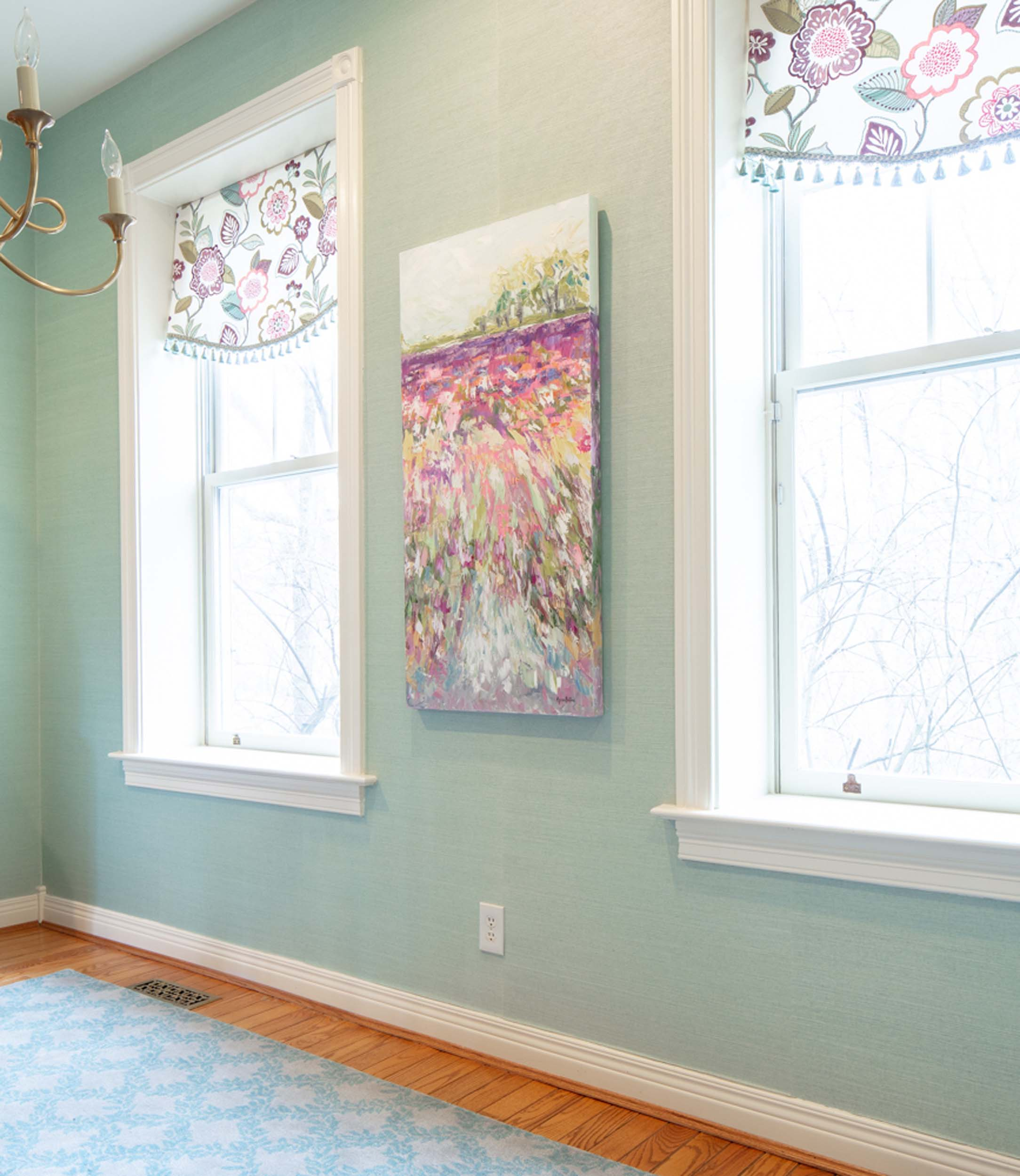 Mint green wall with colorful artwork and two large windows