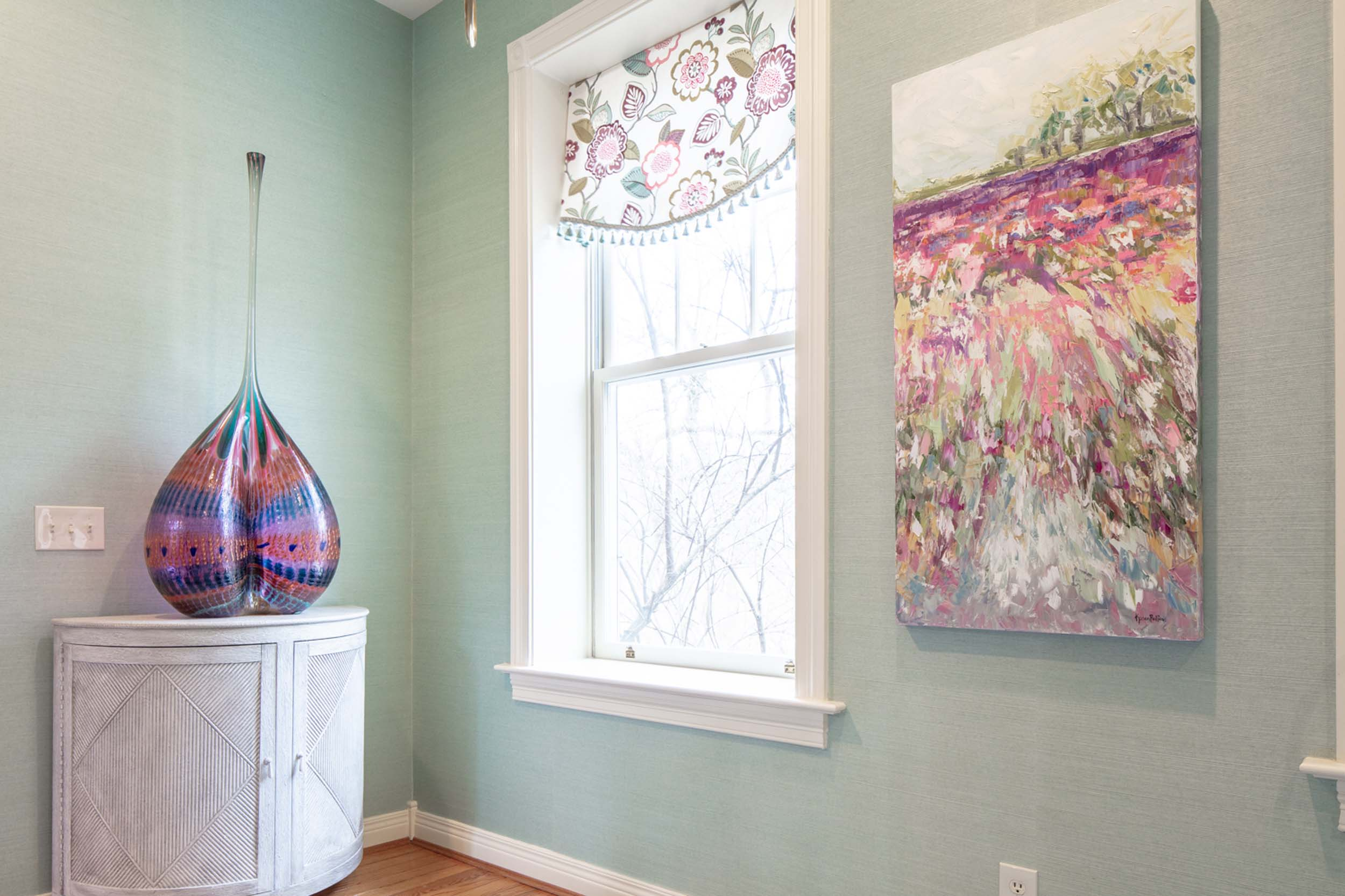 Mint green room with large window and artwork on the wall