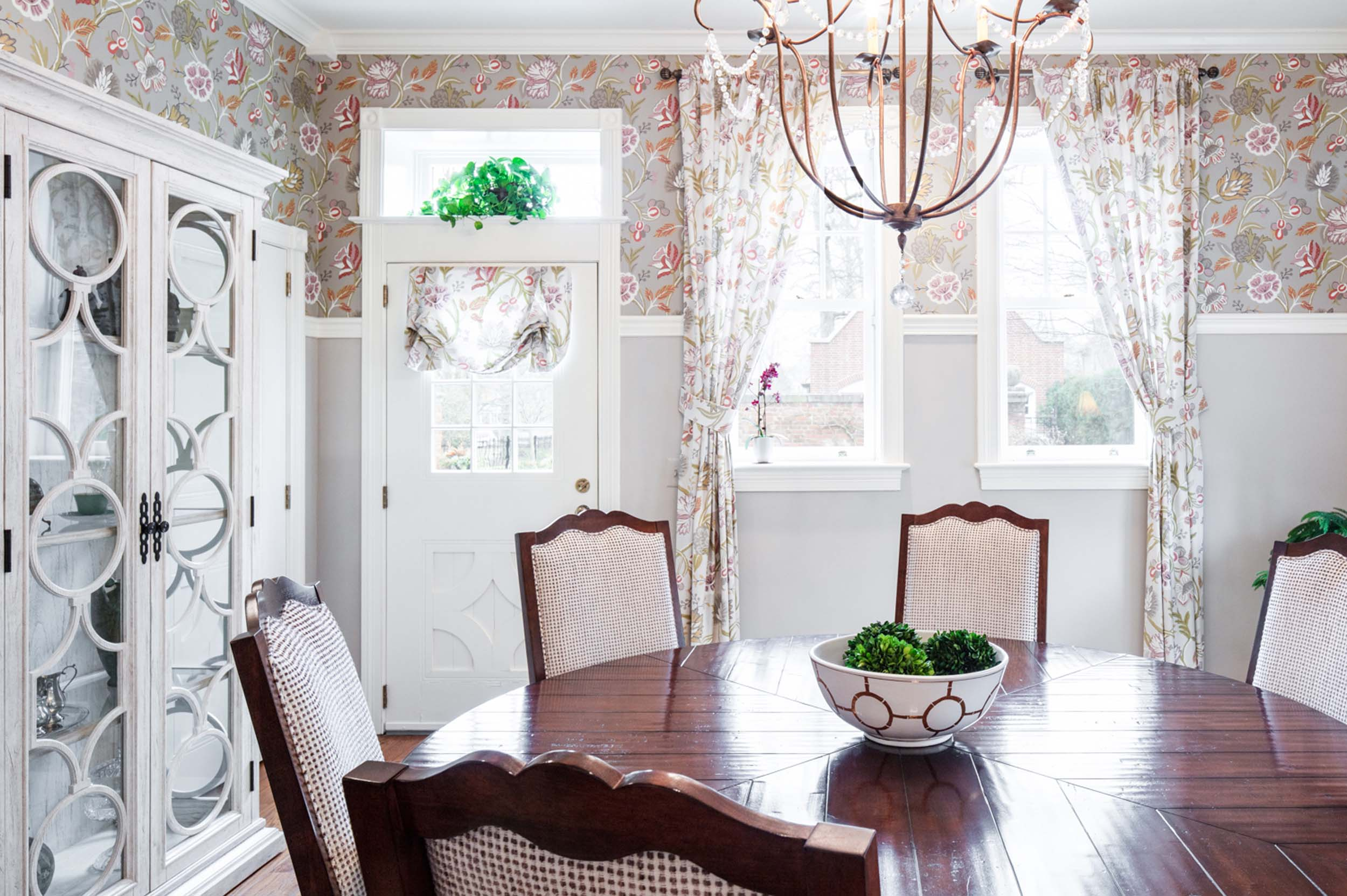 Dining area with white door, round wooden table and chairs