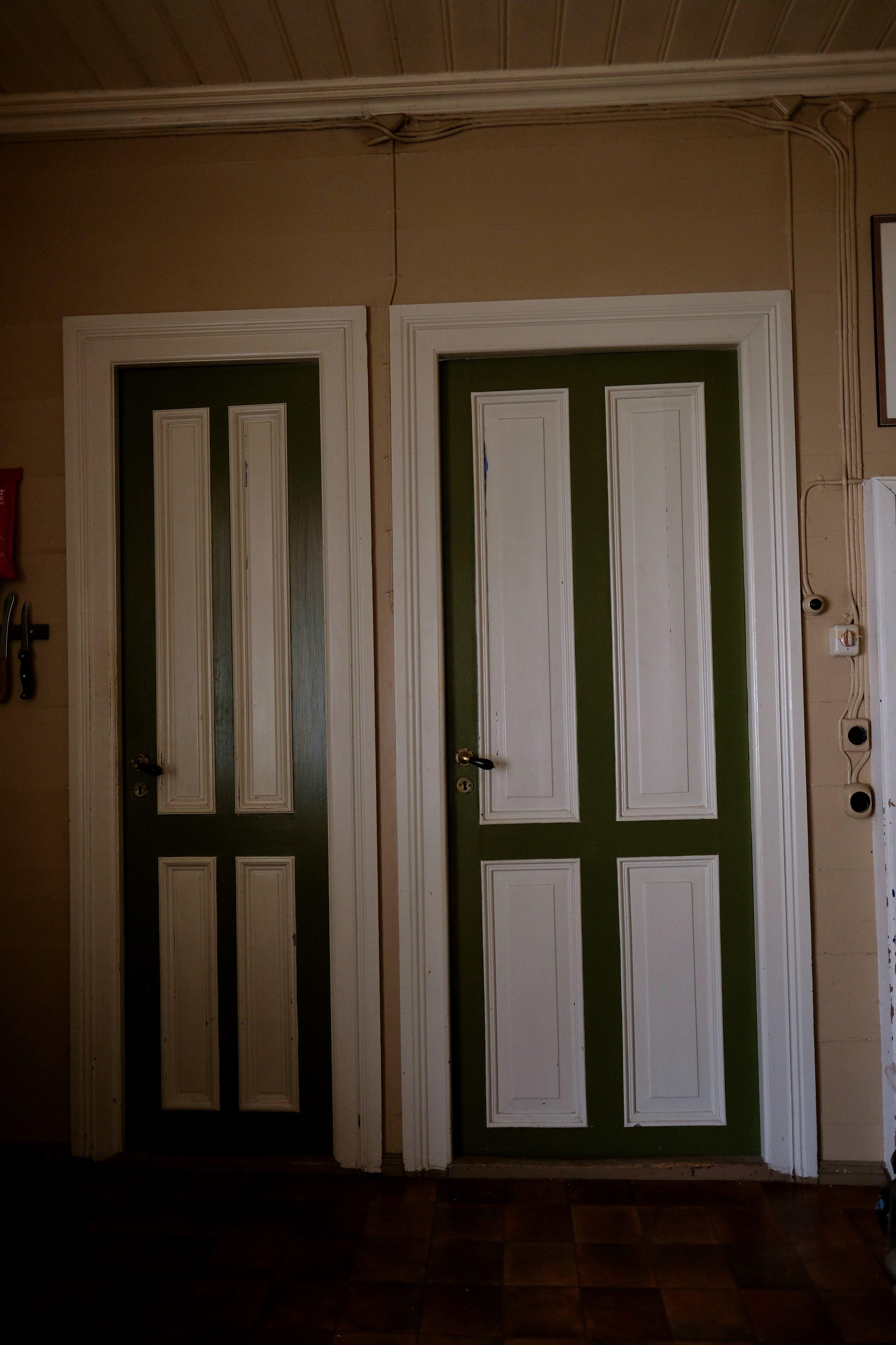 Ei stor og ei lita dør. Døra inn til venstre er til matkammerset, døra til høgre er inn til det blå rommet. Desse dørene er på kjøkenet der ein har heile 5 dører.