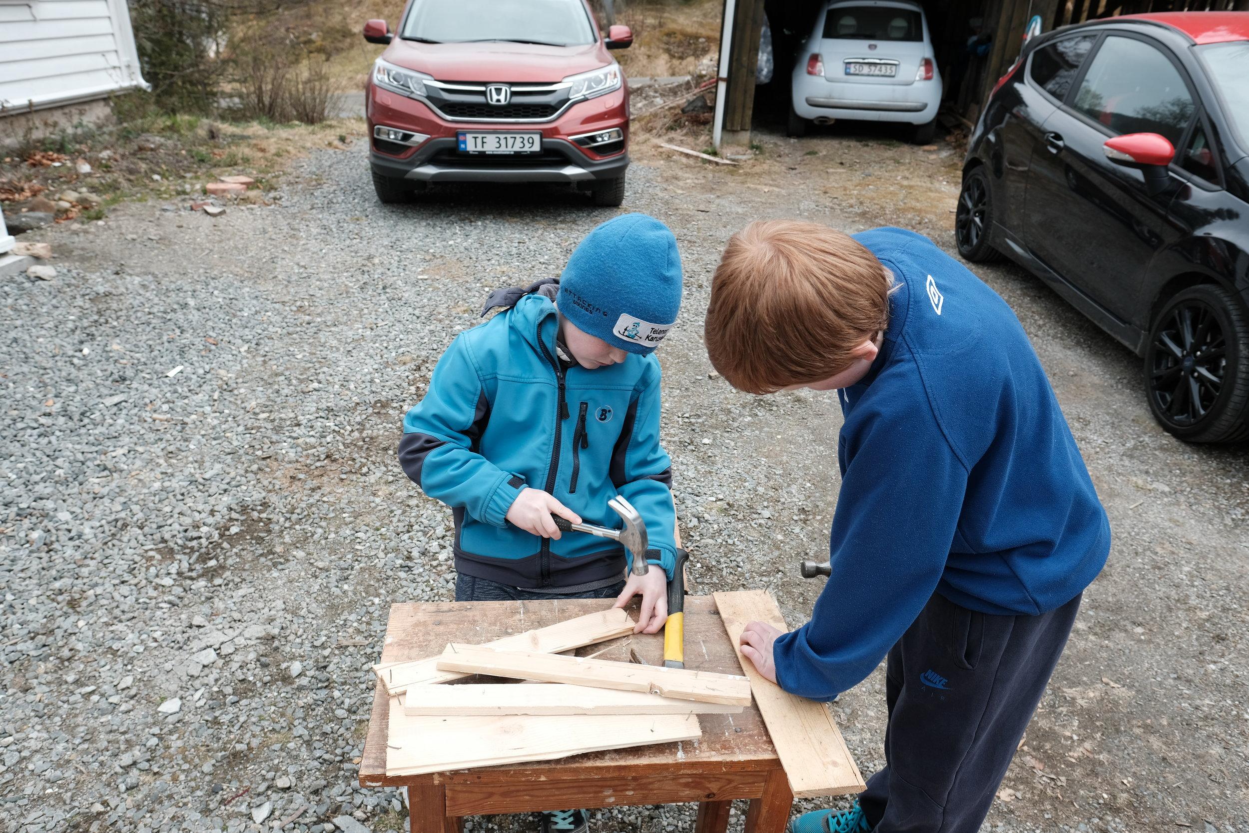 To andre ivrige hjelparar hjelper til med å fjerna spikar frå eit anna panel