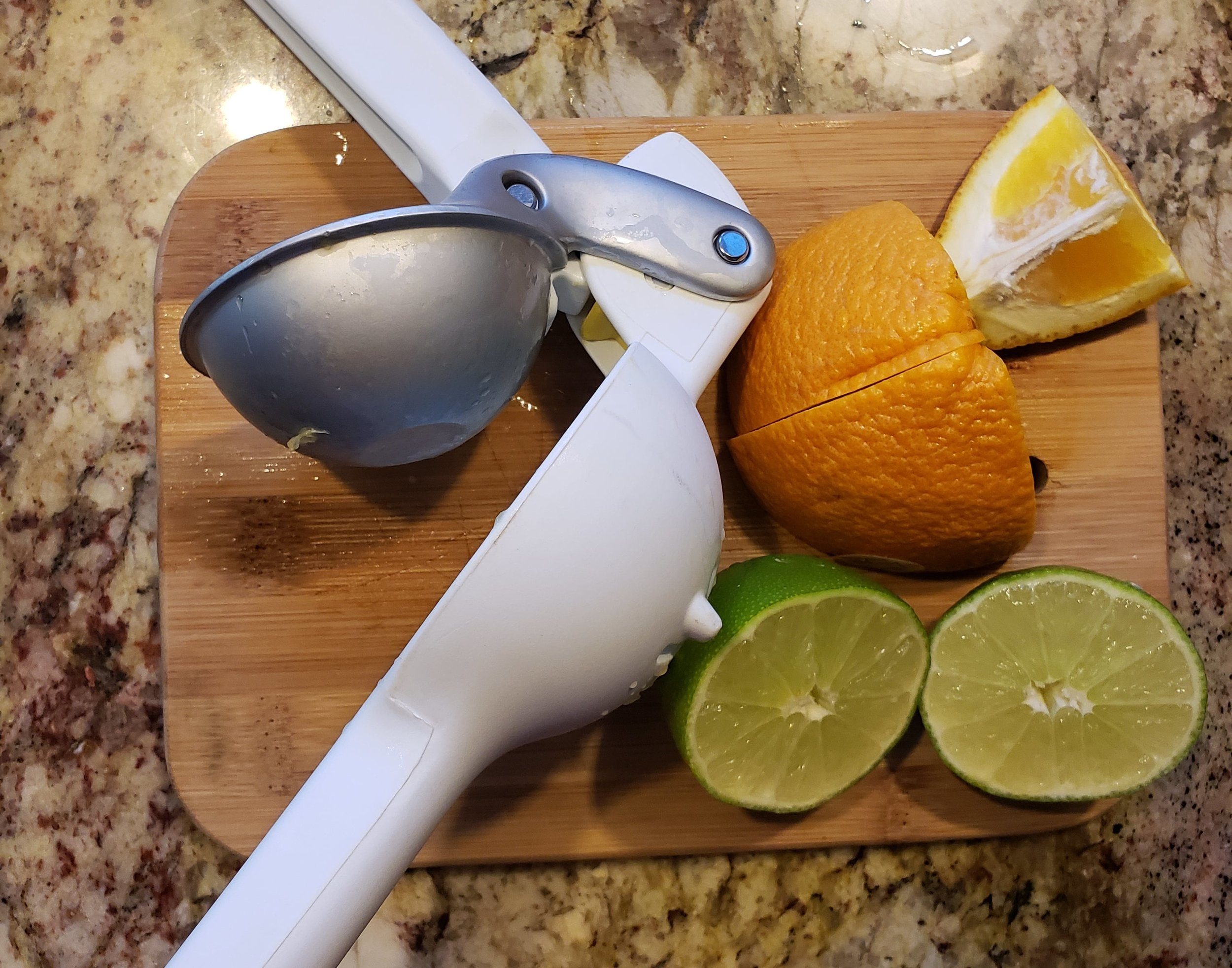 Hand citrus juicer with fresh sliced oranges and limes.