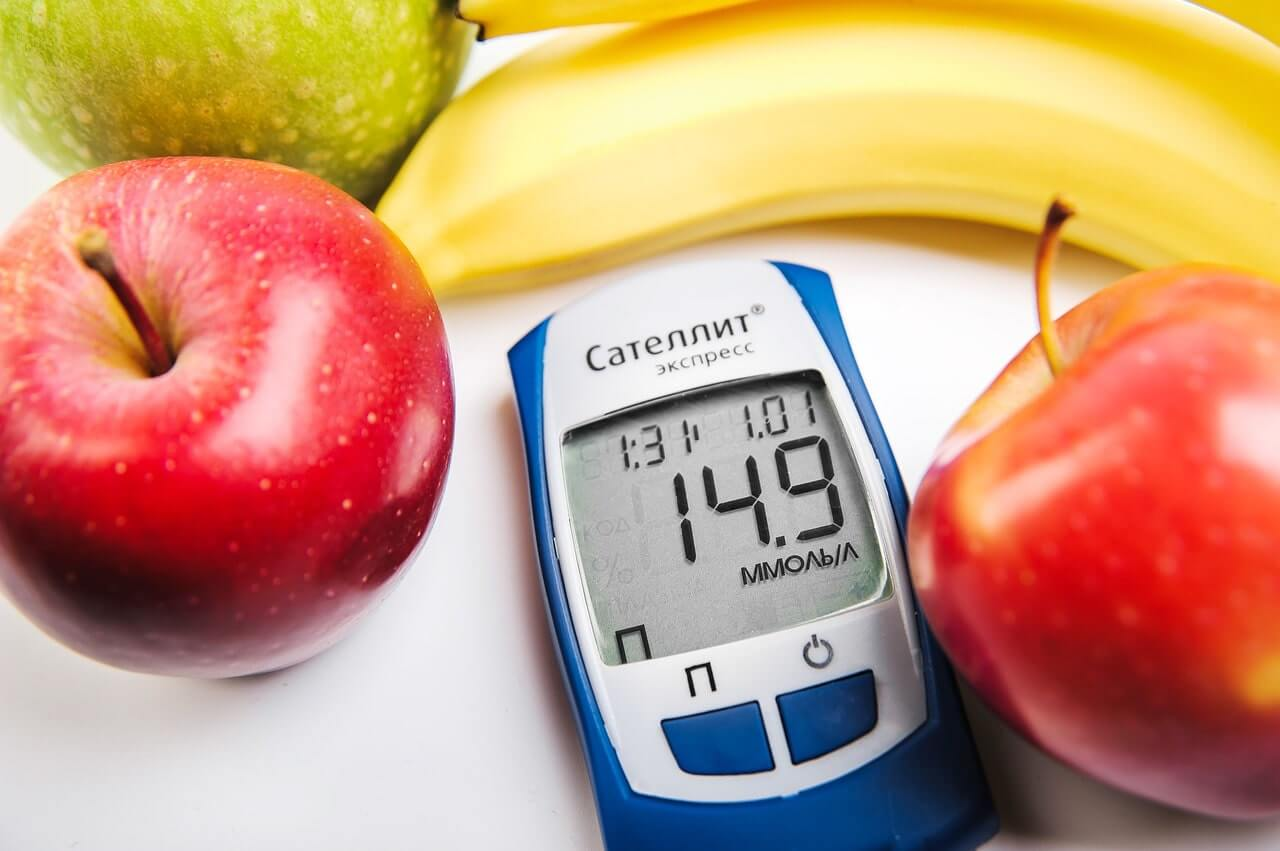 Diabetes 101- picture of a blood glucose monitor surrounded by fruit.