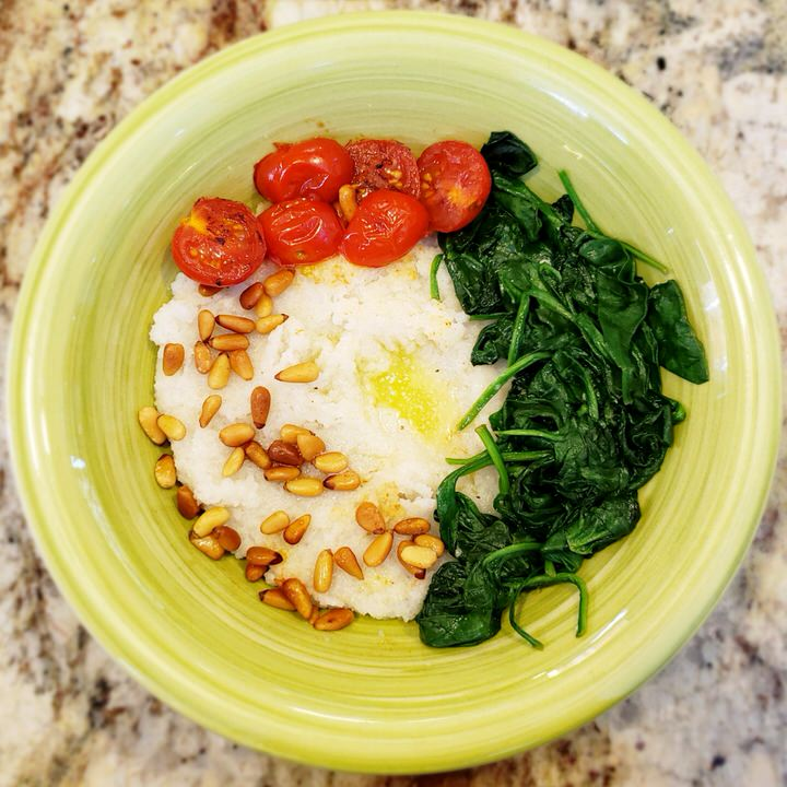 Fonio grain bowl topped with spinach, pine nuts, and tomato.