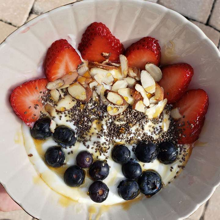 Yogurt bowls with strawberries, blueberries, almonds, and chia seeds.