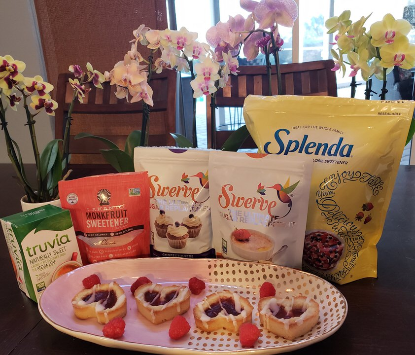 Splenda, swerve, truvia, monkfruit sweetener on the table with cookies.