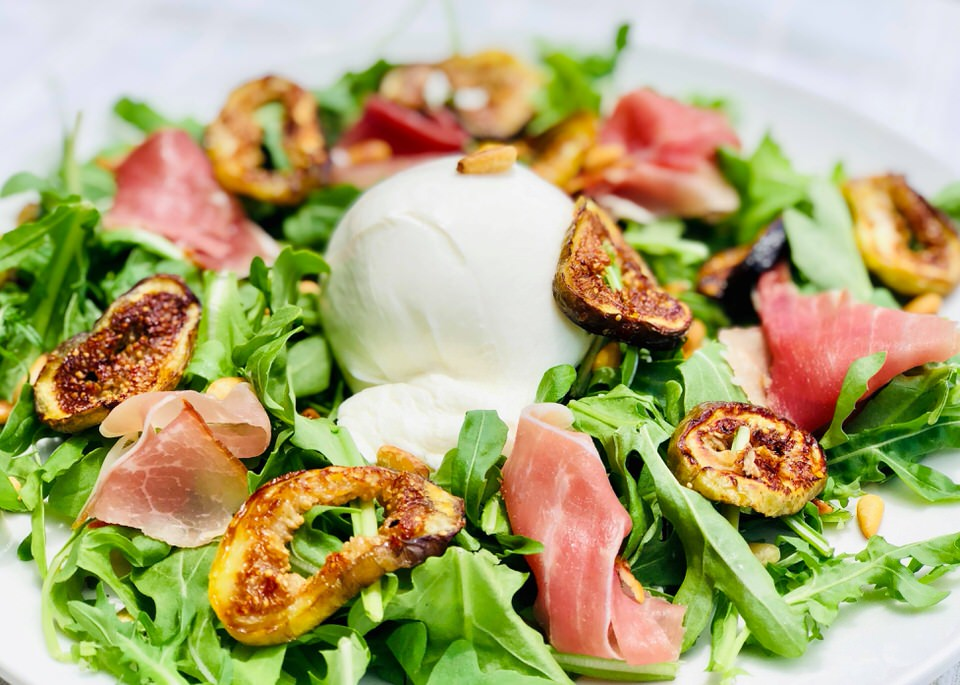 Roasted fig and prosciutto salad with burrata cheese on top.