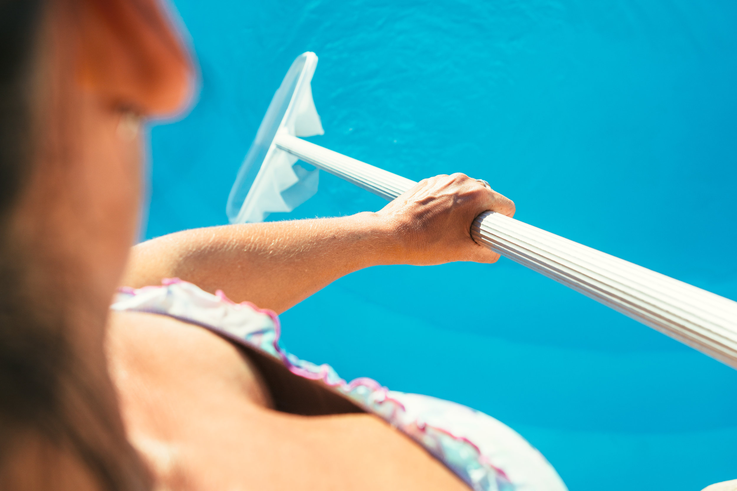 A cropped photograph of a woman using a skimmer net in her pool.
