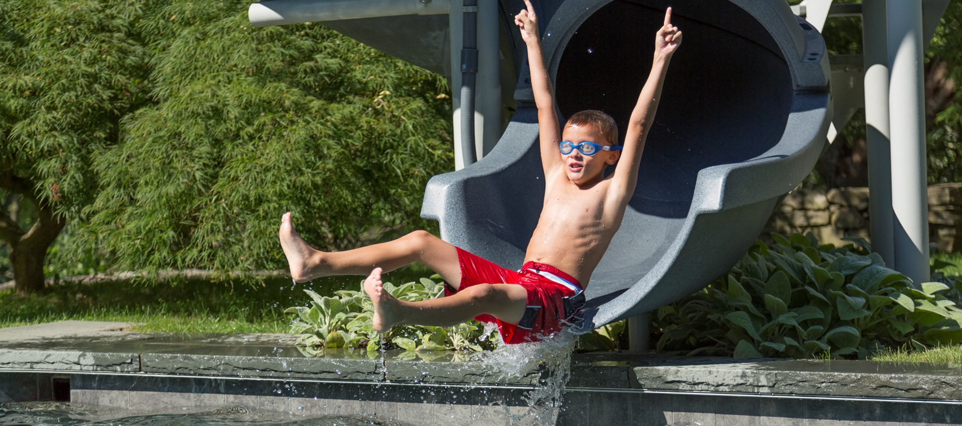 A young boys comes down a slide into his backyard pool.