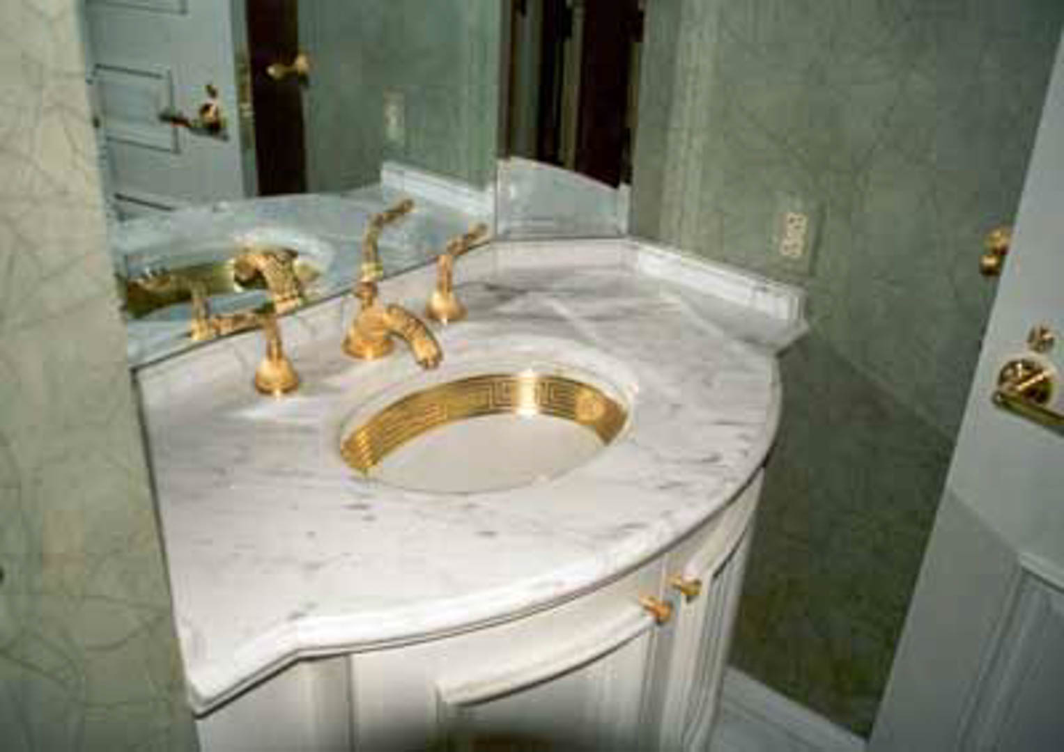 Project:  Caesars Palace Hotel   Location:  Las Vegas, Nevada   Description:   Custom fabrication is an everyday expertise for Carrara Marble Company. Here you see a beautiful marble bathroom vanity top with gold trim and faucet designed for a luxury suite.