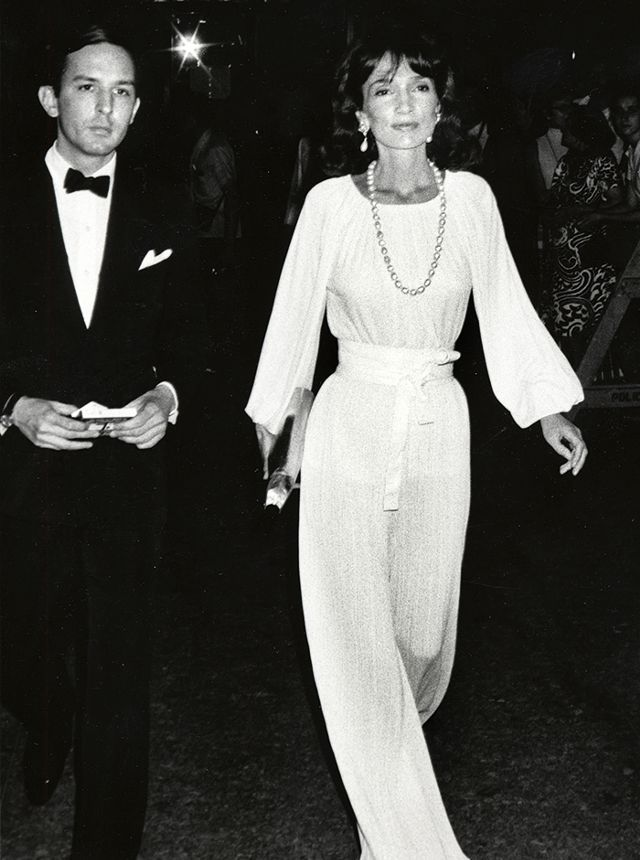 Lee Radziwill wears a white belted jumpsuit with a large pearl necklace, statement earrings, and a metallic clutch.jpg