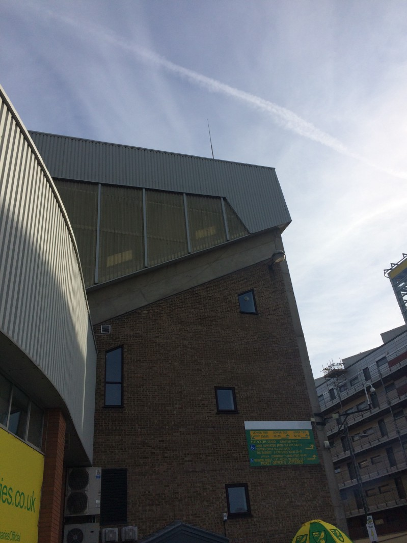 The conjunction of the River End and main stand (left) accidentally offers a rare moment of architectural interest. In the background, the Wensum-backing Rotterdammish flats.