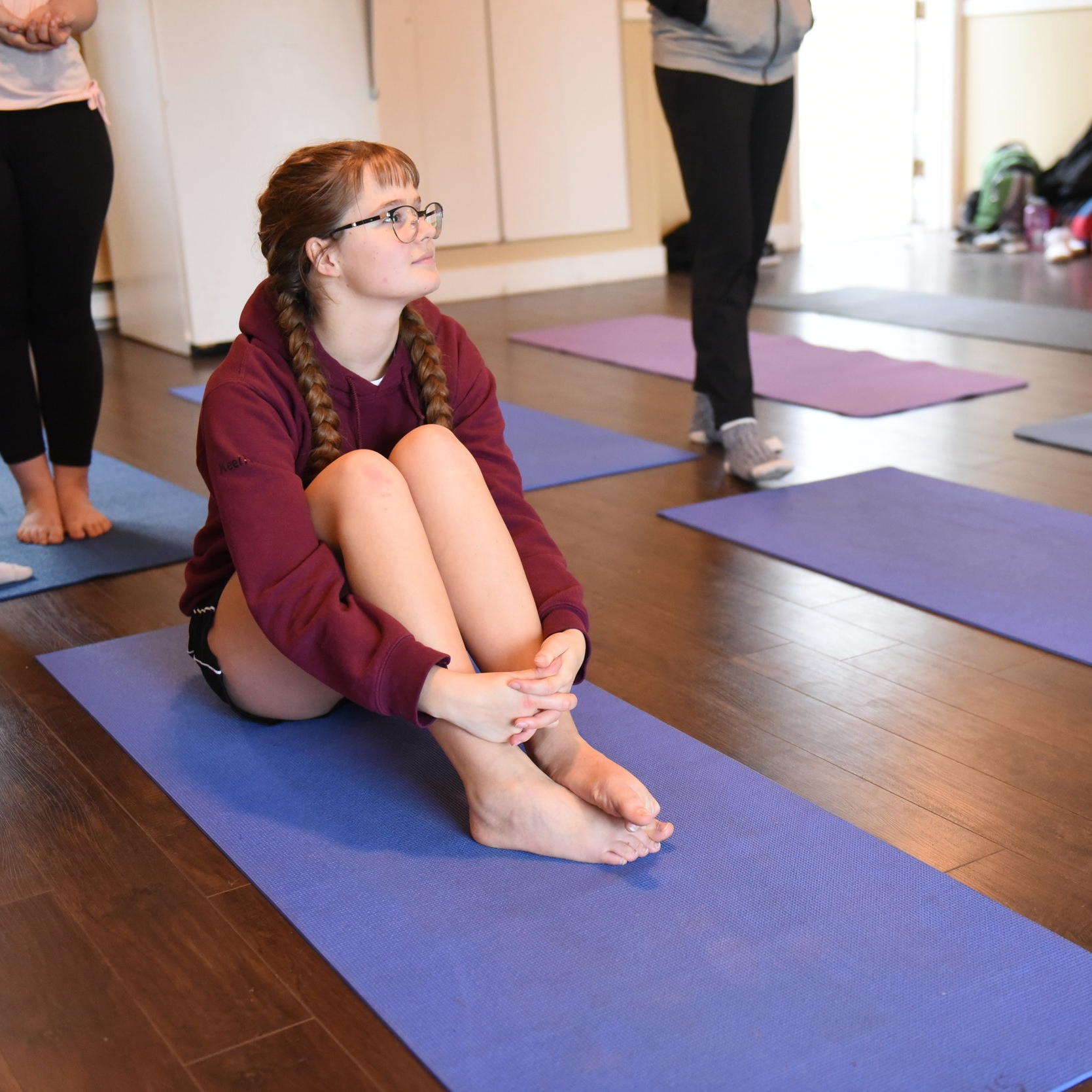 A student sits in the yoga studio, contemplating the new skills she has learned that day.