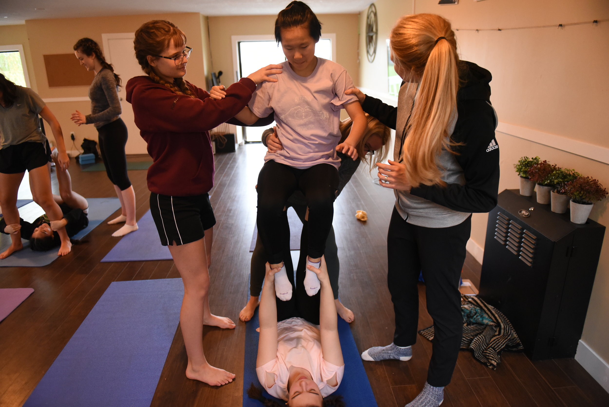 Mandy Rosts supports a student as she tries Acro Yoga for the first time, led by Katie Thacker