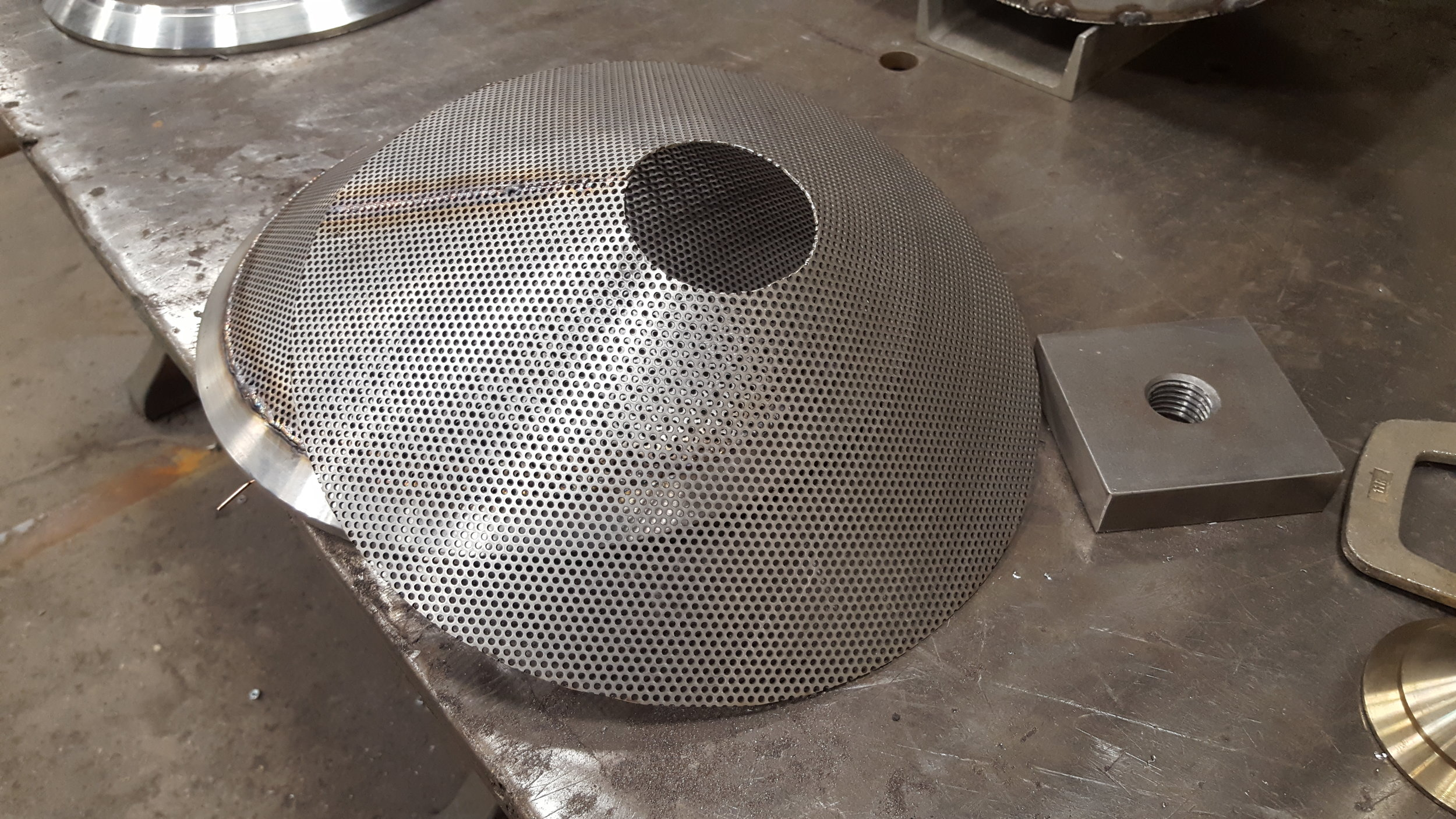 These perforated metal screens are used to remove process fluids from manufactured parts. They are assembled and welded into housings which are fabricated in-house as well.