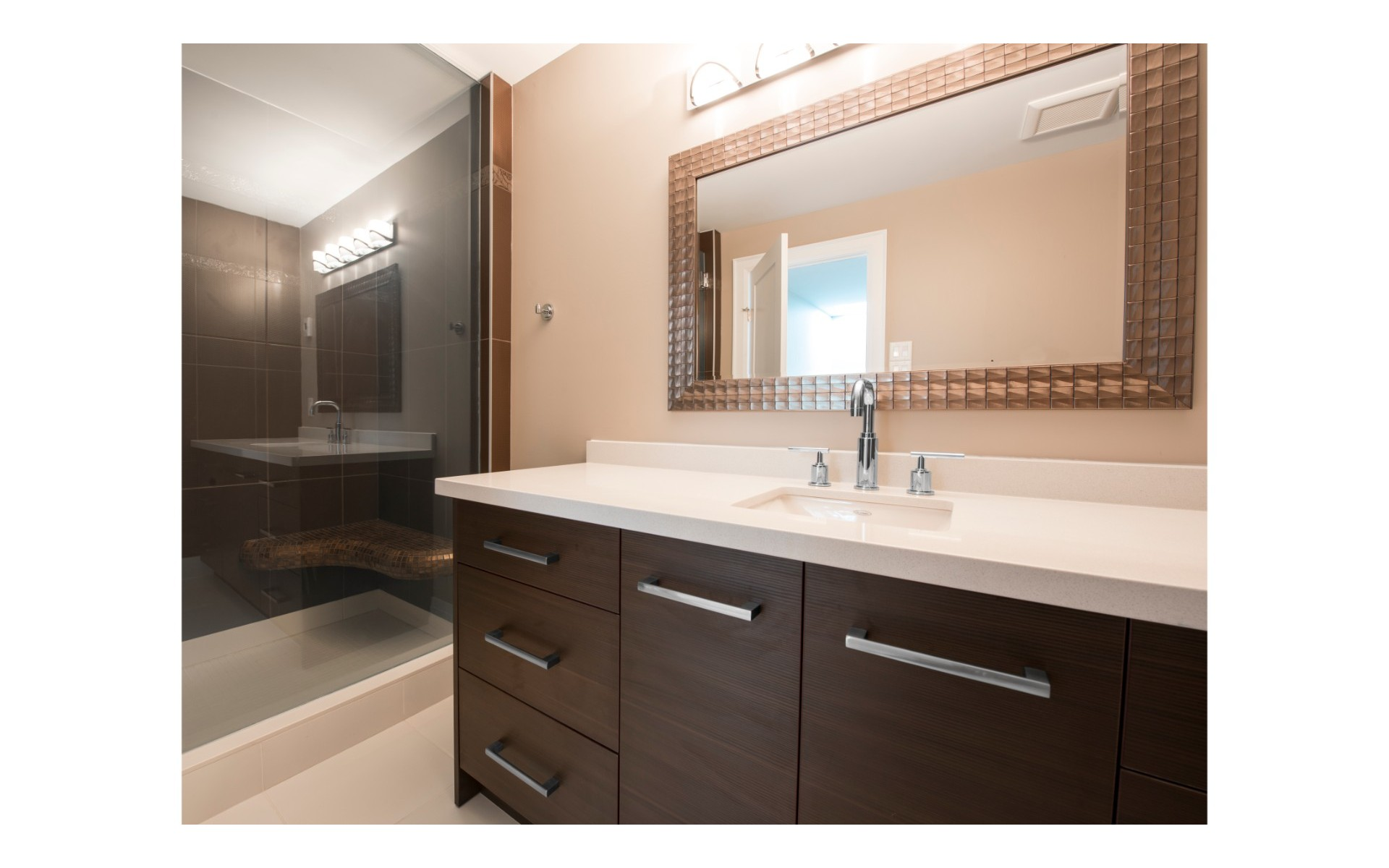 Dark wood vanity with stainless steel accents and light countertop