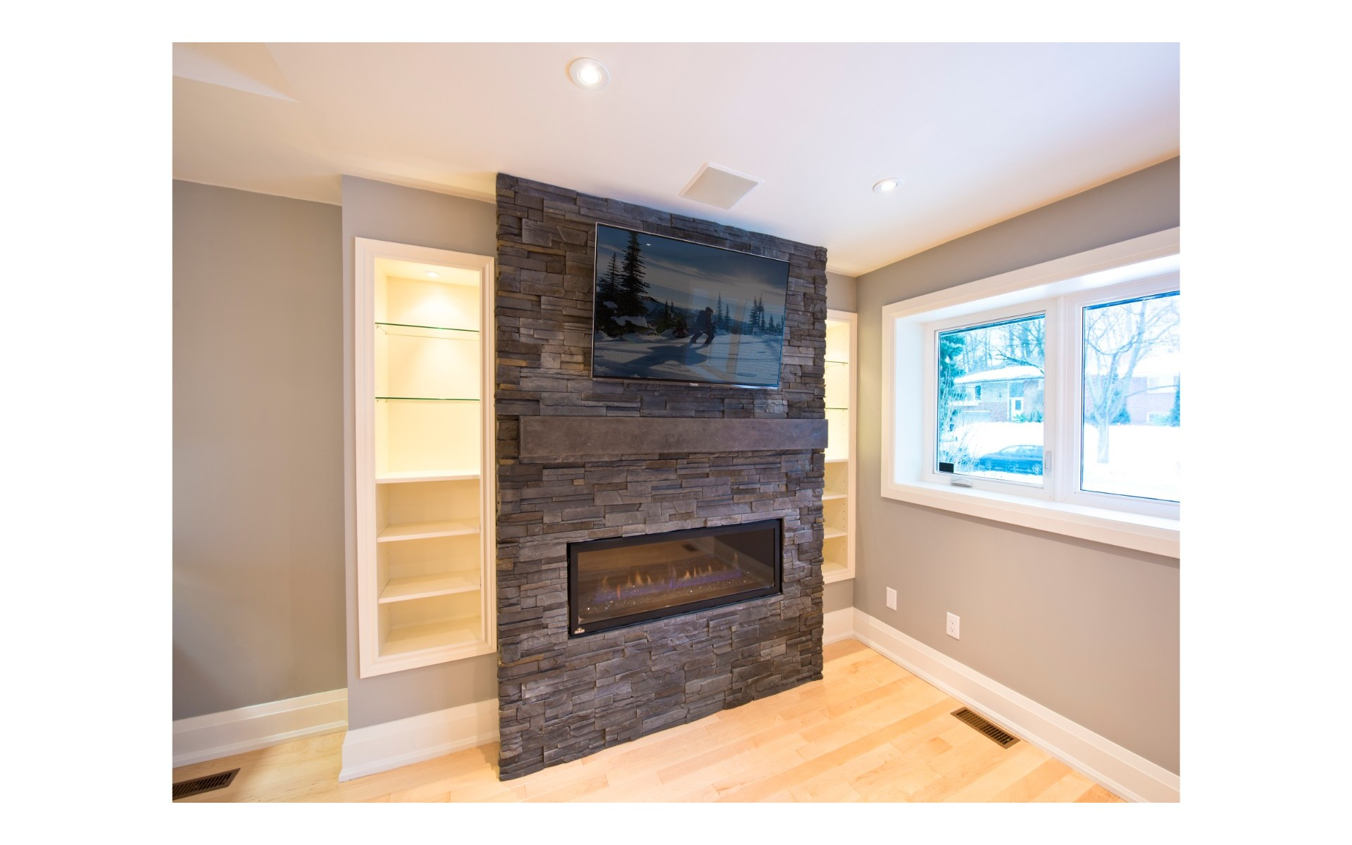 TV mounted above electric fireplace with dark accents