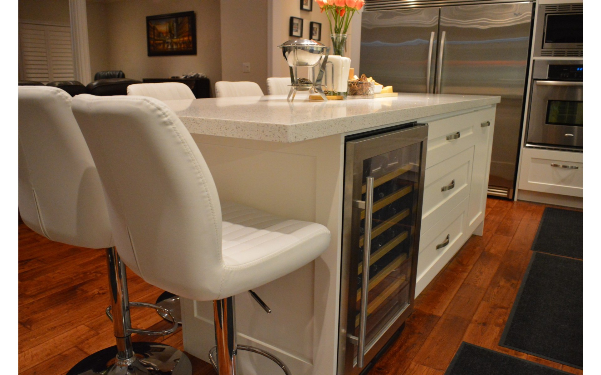 White kitchen island with white leather chairs and built in wine fridge