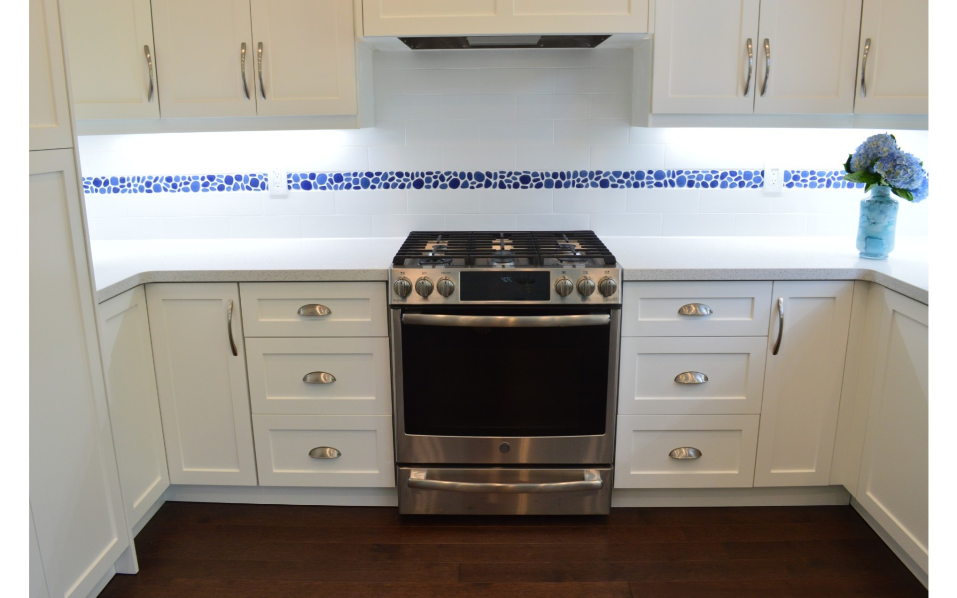 Kitchen with white cabinets, white underlight and stainless steel appliances