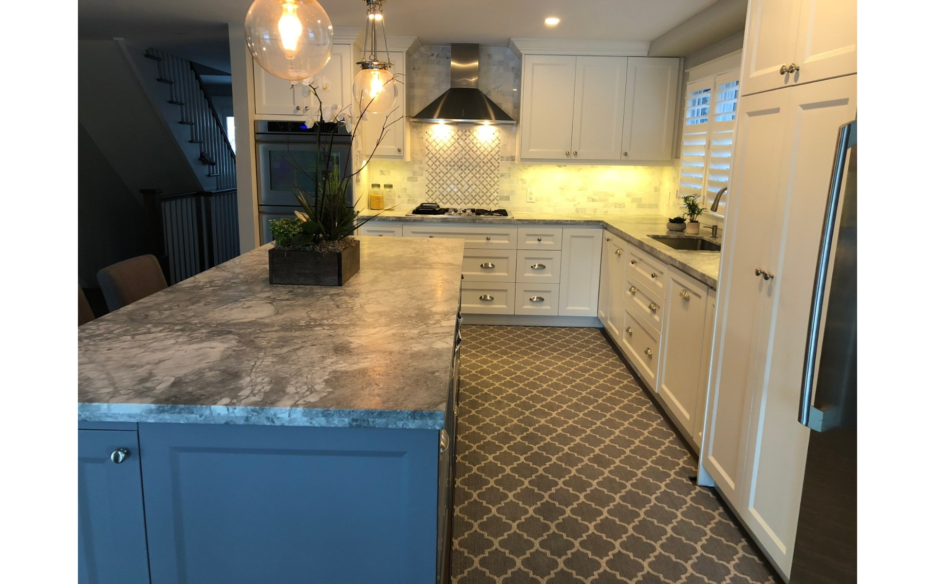 Kitchen with white cabinets, dark checked floor and stone countertop
