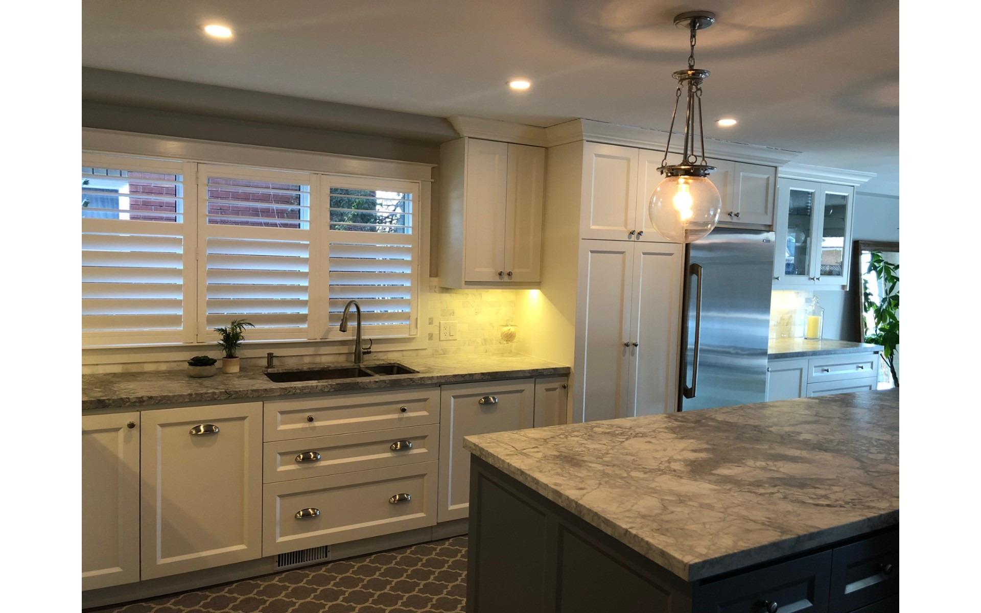 Kitchen with white cabinets, dark patterned floor and stone countertop