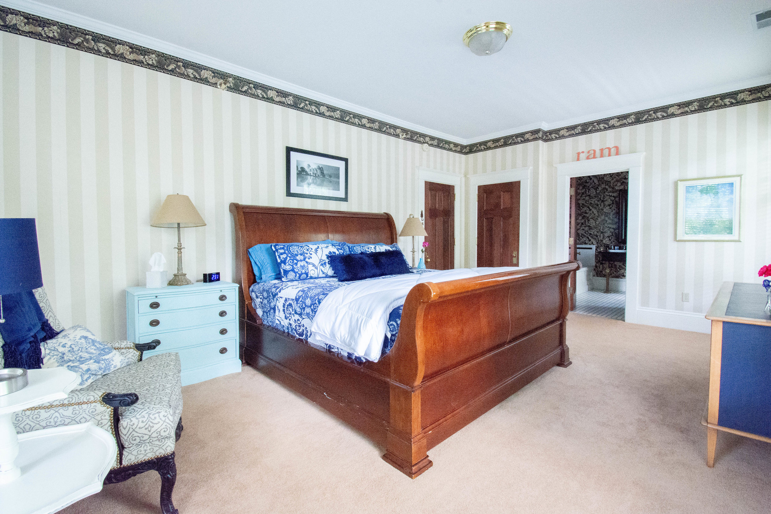 "<img alt= ""full view of room from left side of bed including view into bathroom and hall"" />"