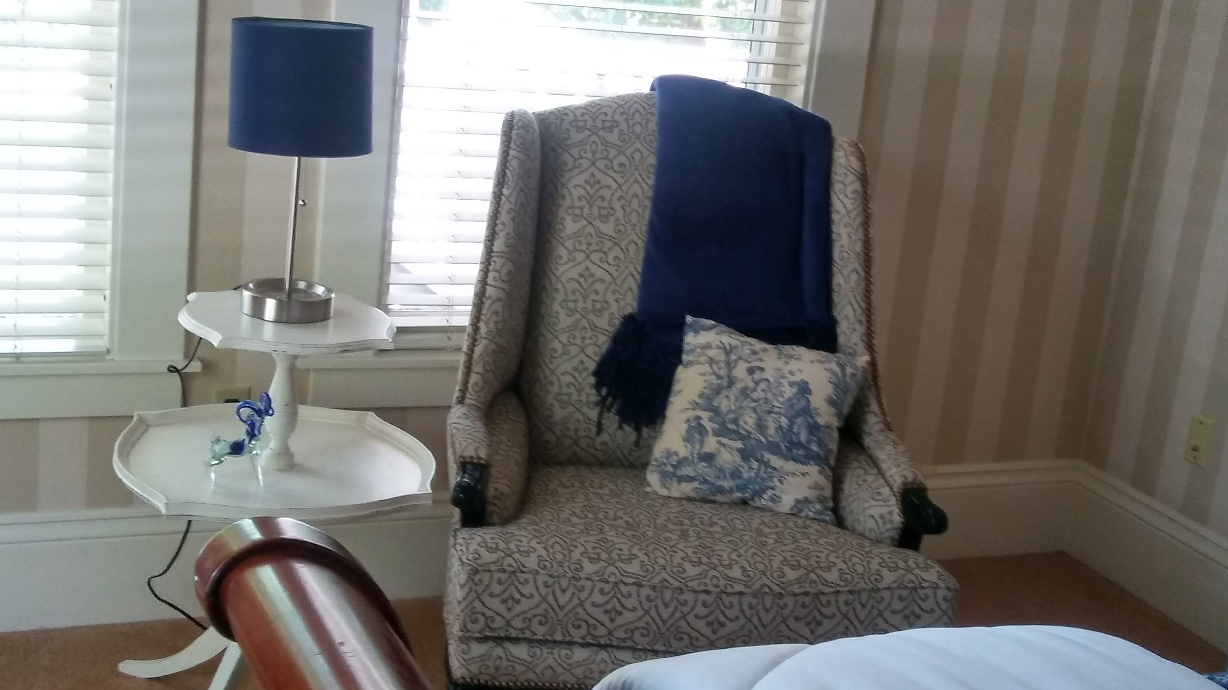 "<img alt= ""Patterned chair with blue throw and table with small lamp"" />"