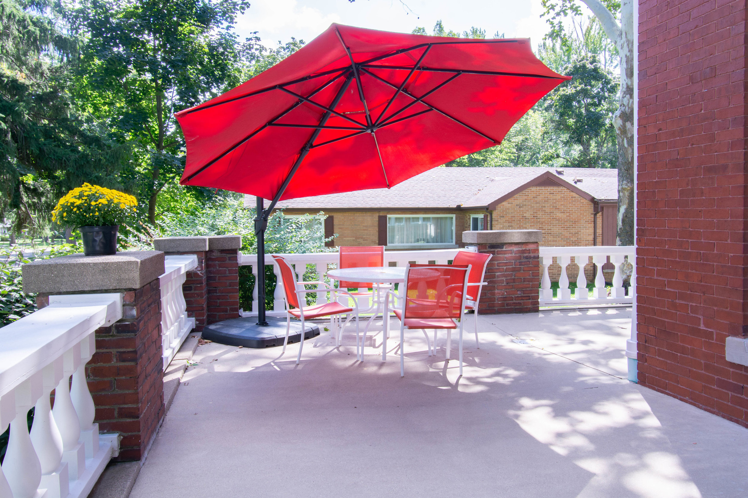 "<img alt= ""Large red umbrella and patio table with four chairs on front porch"" />"