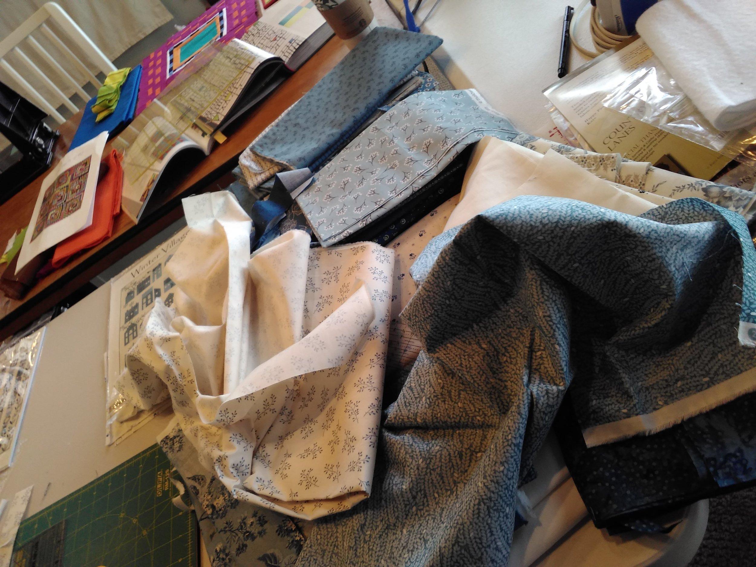 "alt=""Piles of fabric"""