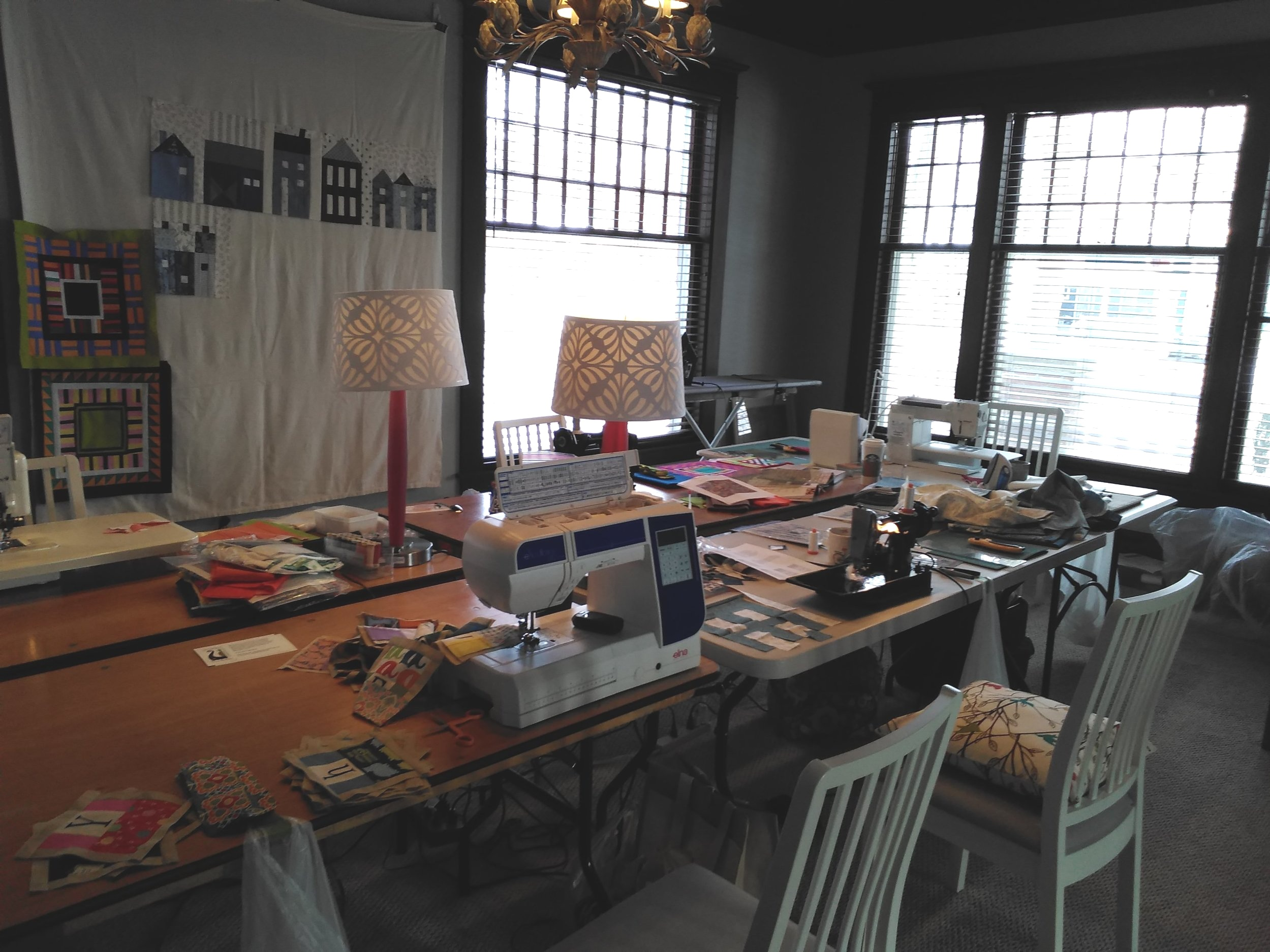 """alt=""""Tables set up for quilting.  With lamps and sewing machines"""""""