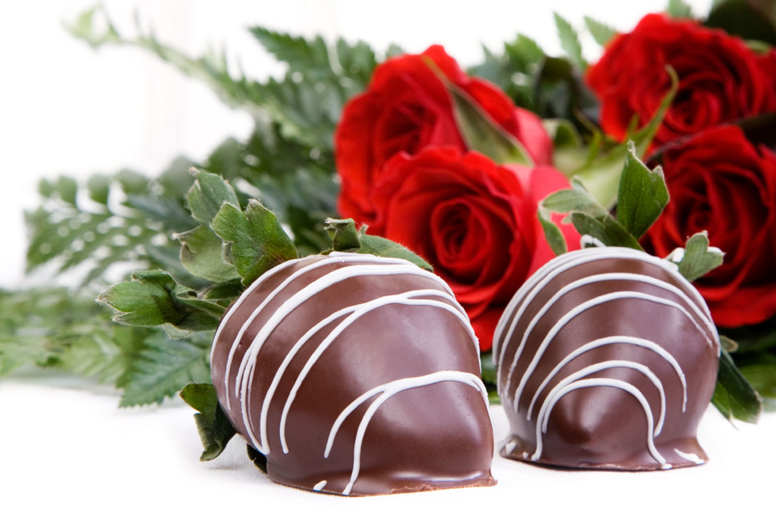 alt='2 Chocolate covered strawberries with red roses laying in the background'