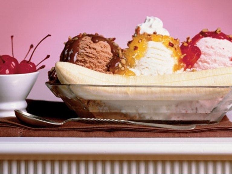 alt='Banana split with chocolate, vanilla and strawberry ice cream and toppings.  Sundae spoon laying in front of the ice cream and a bowl of cherries to the left.'