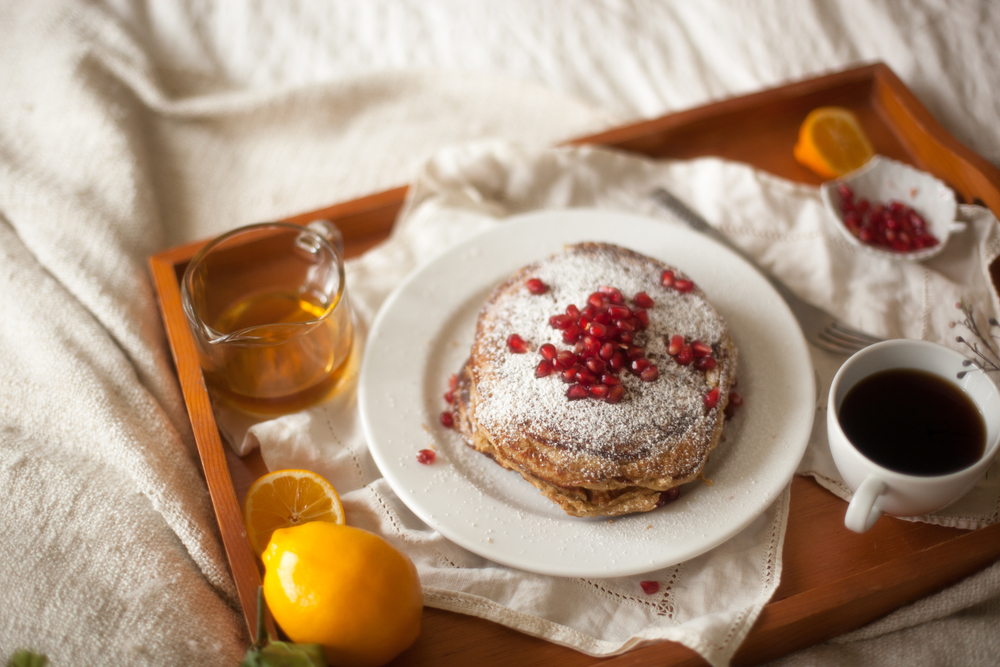 alt='Stack of pancakes with pomegranates and powdered sugar. Also lemons, syrup and coffee on a breakfast tray laying on a bed.'