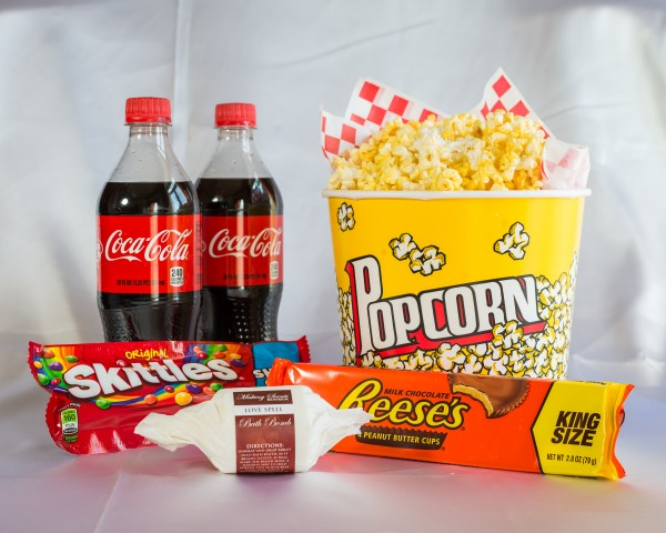 alt='2 20-ounce bottles of coca-cola, one bag of skittles, on king-sized package of reese's peanut butter cups along with a large bucket of popcorn.'