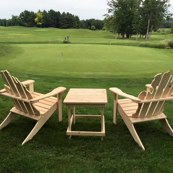 "alt=""Two Adirondack chairs overlooking the putting green at The Emerald Golf Course"""