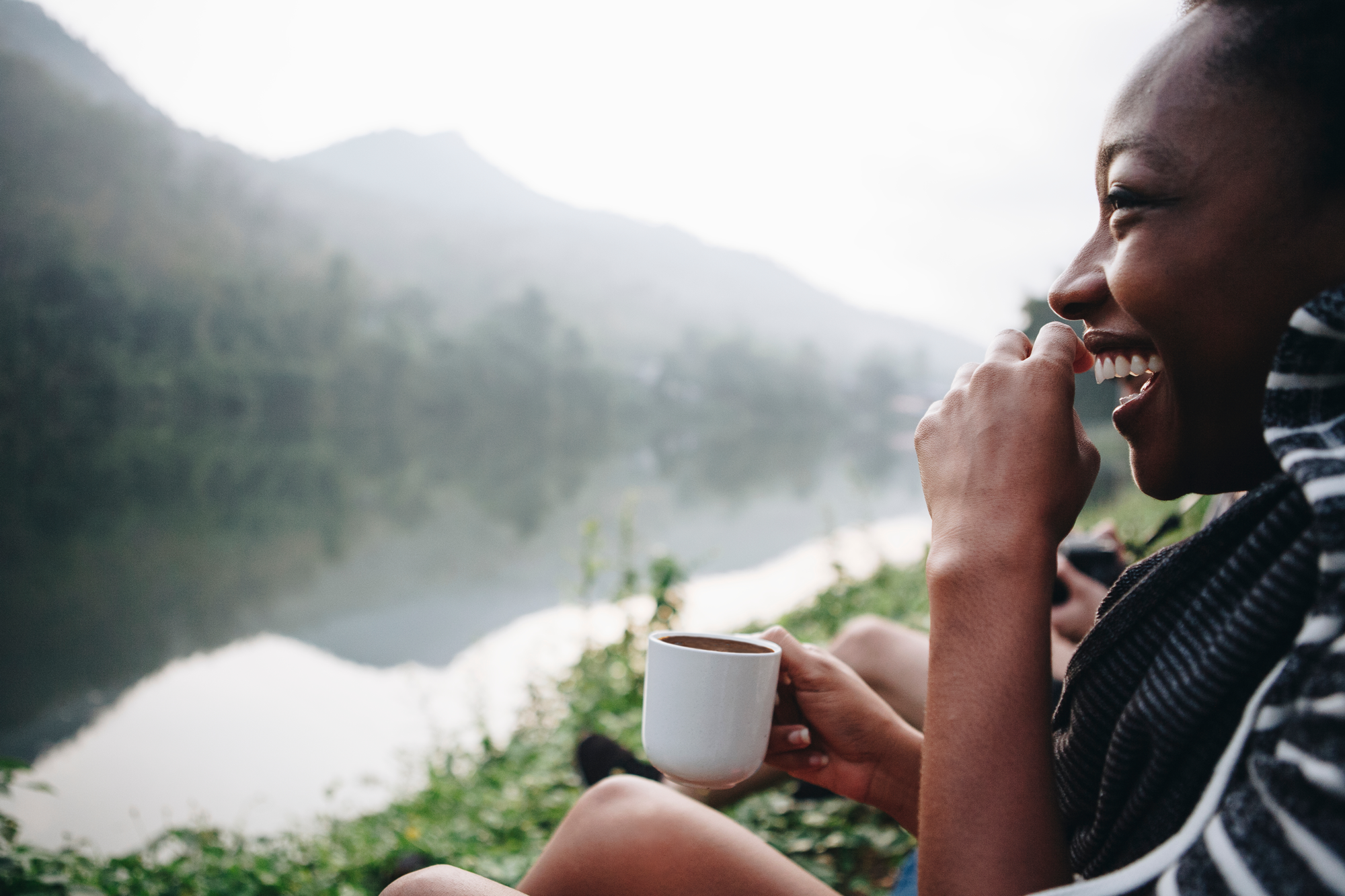 woman laughing sitting along river with cup of cacao