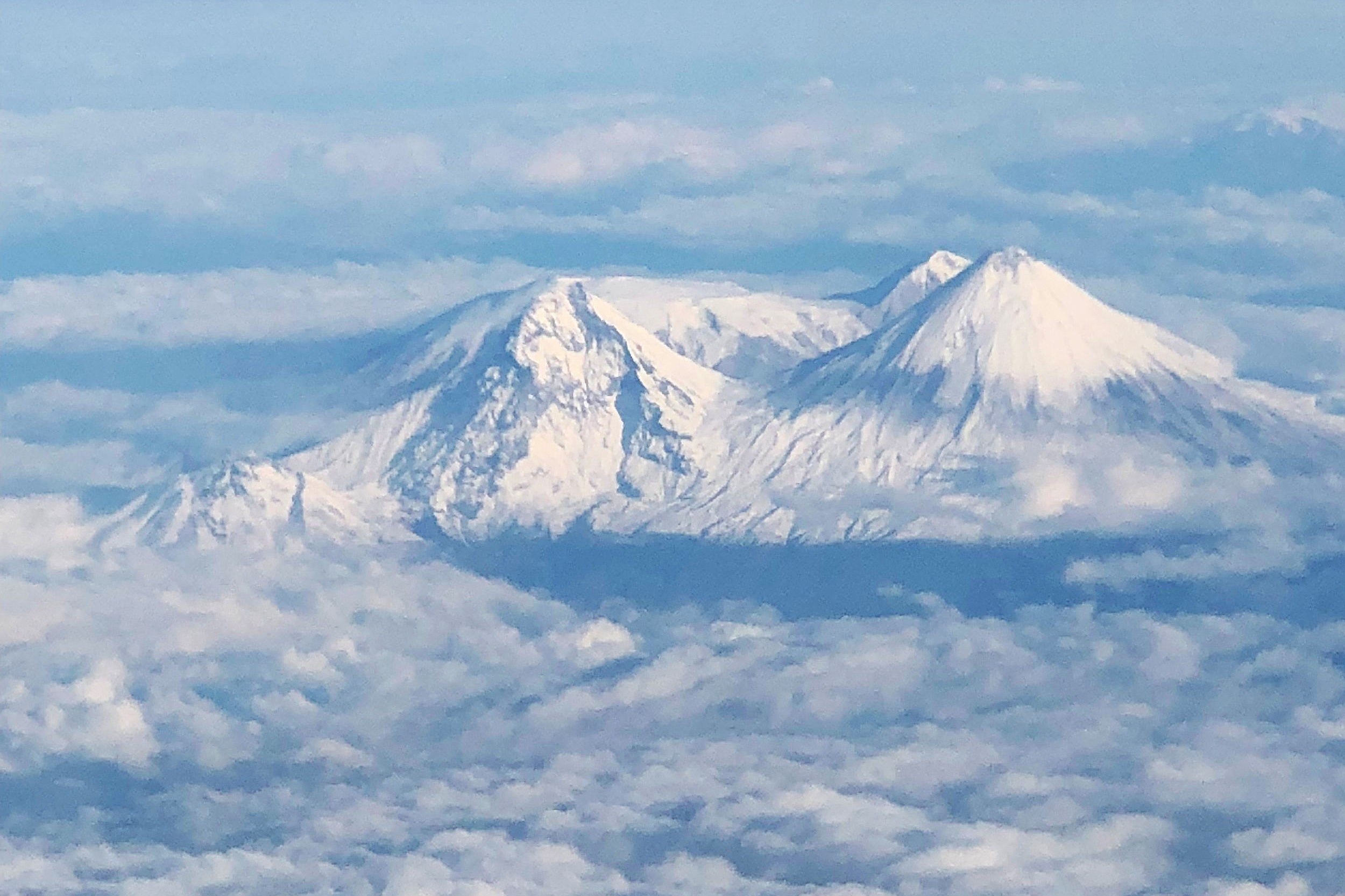 Kamchatka's Volcanos viewed from the Charter flight from Anchorage to Petro. These beautiful volcanoes grace the skyline throughout our trip down the river.