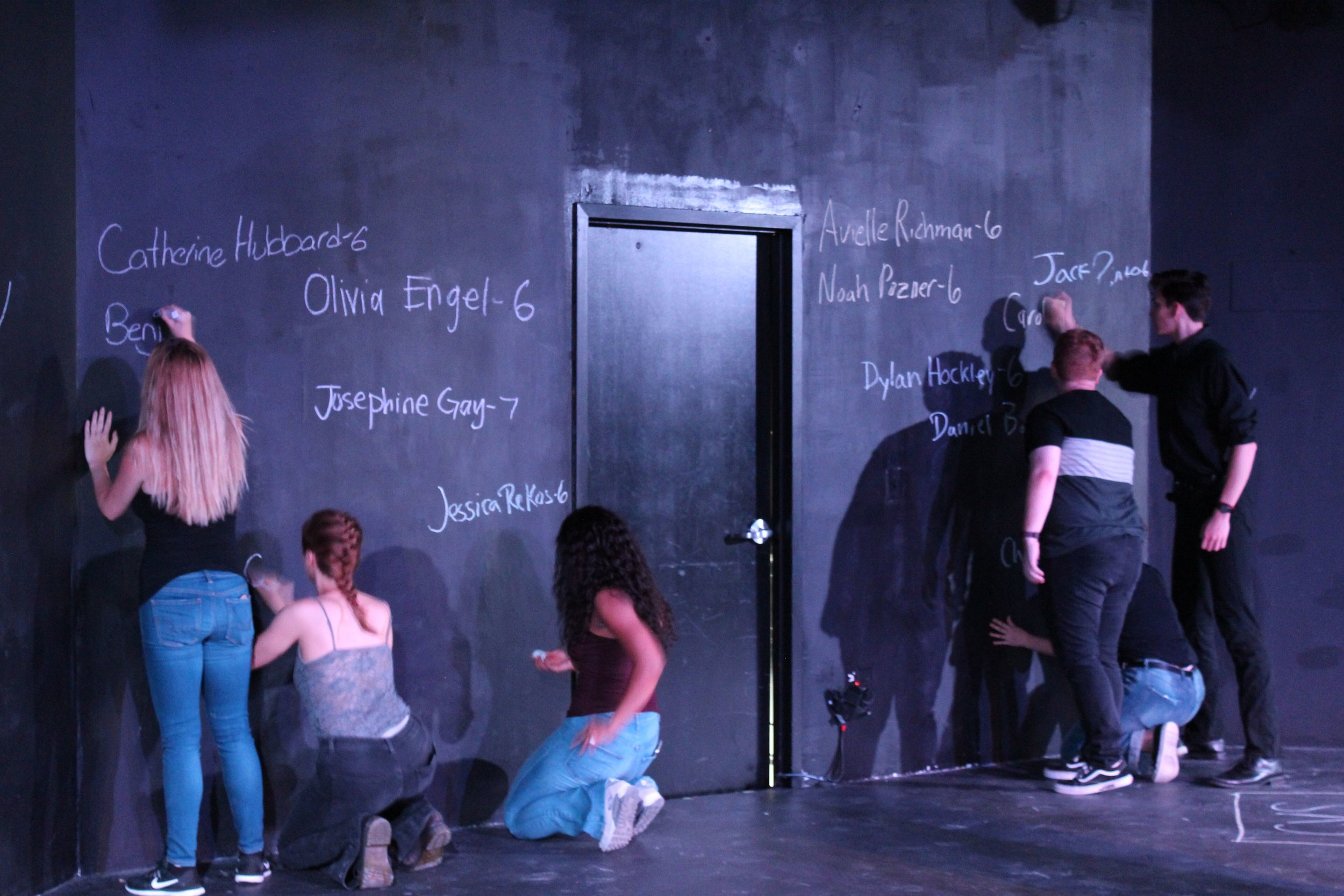 After a difficult scene walking audiences through the events of December 14th, the actors take a moment to write the names of all the victims on the back wall of the theatre. The names remain there for the rest of the play.