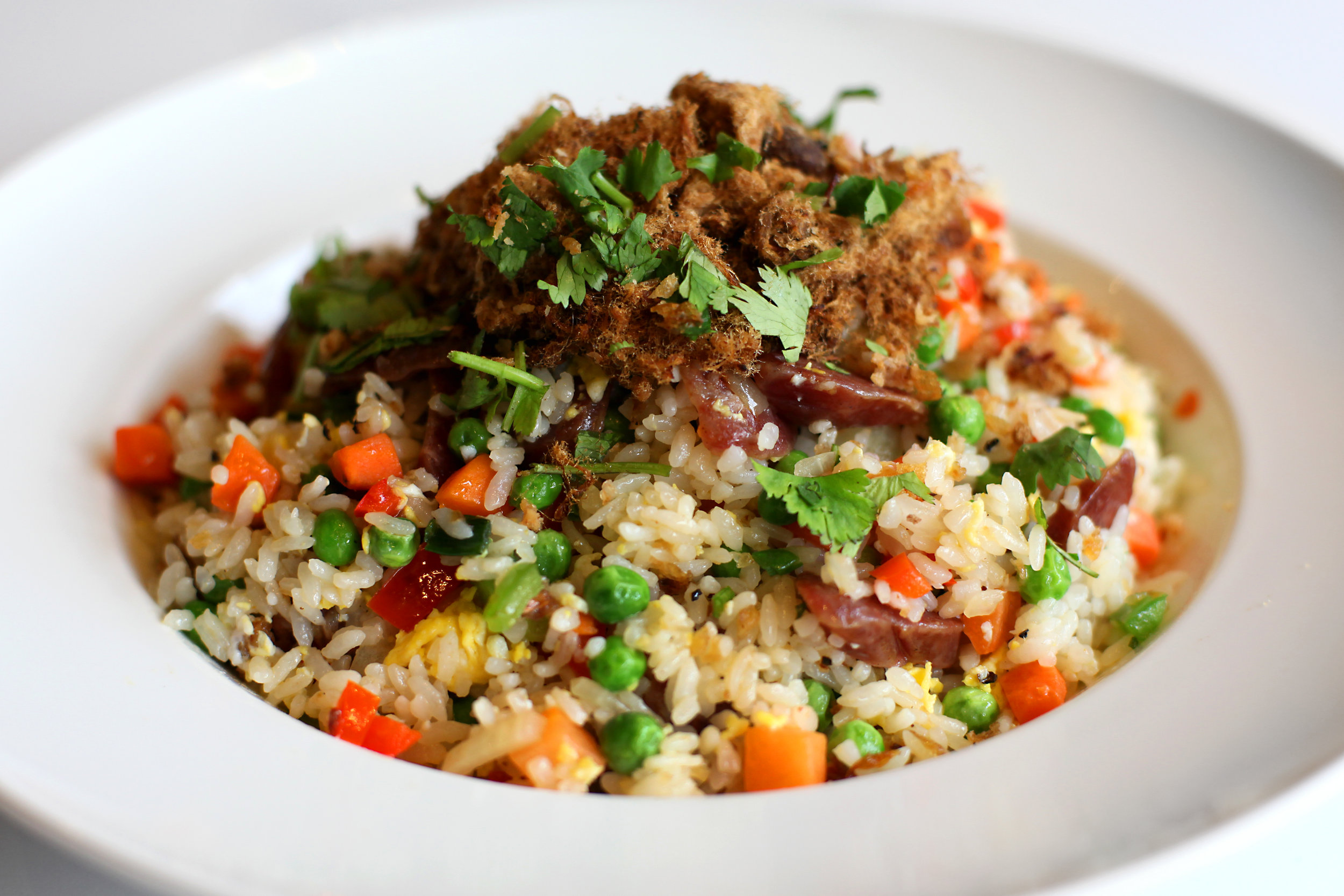 Savory and sweet sausage fried rice with peas and carrots and topped with pork fluff. A homestyle favorite!