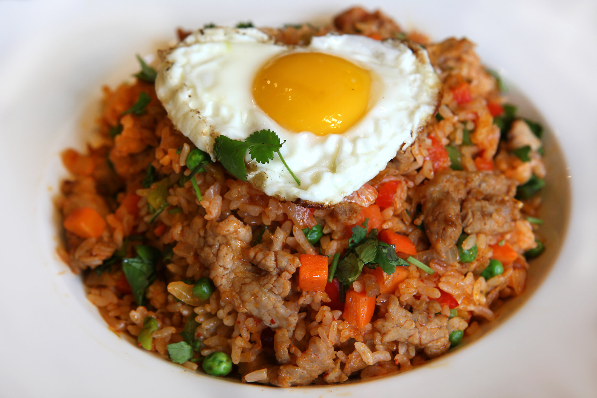 Kimchi Fried Rice: Tender beef strips, kimchi, carrots, peas, and a crispy sunny side up egg combine for a delicious mix.