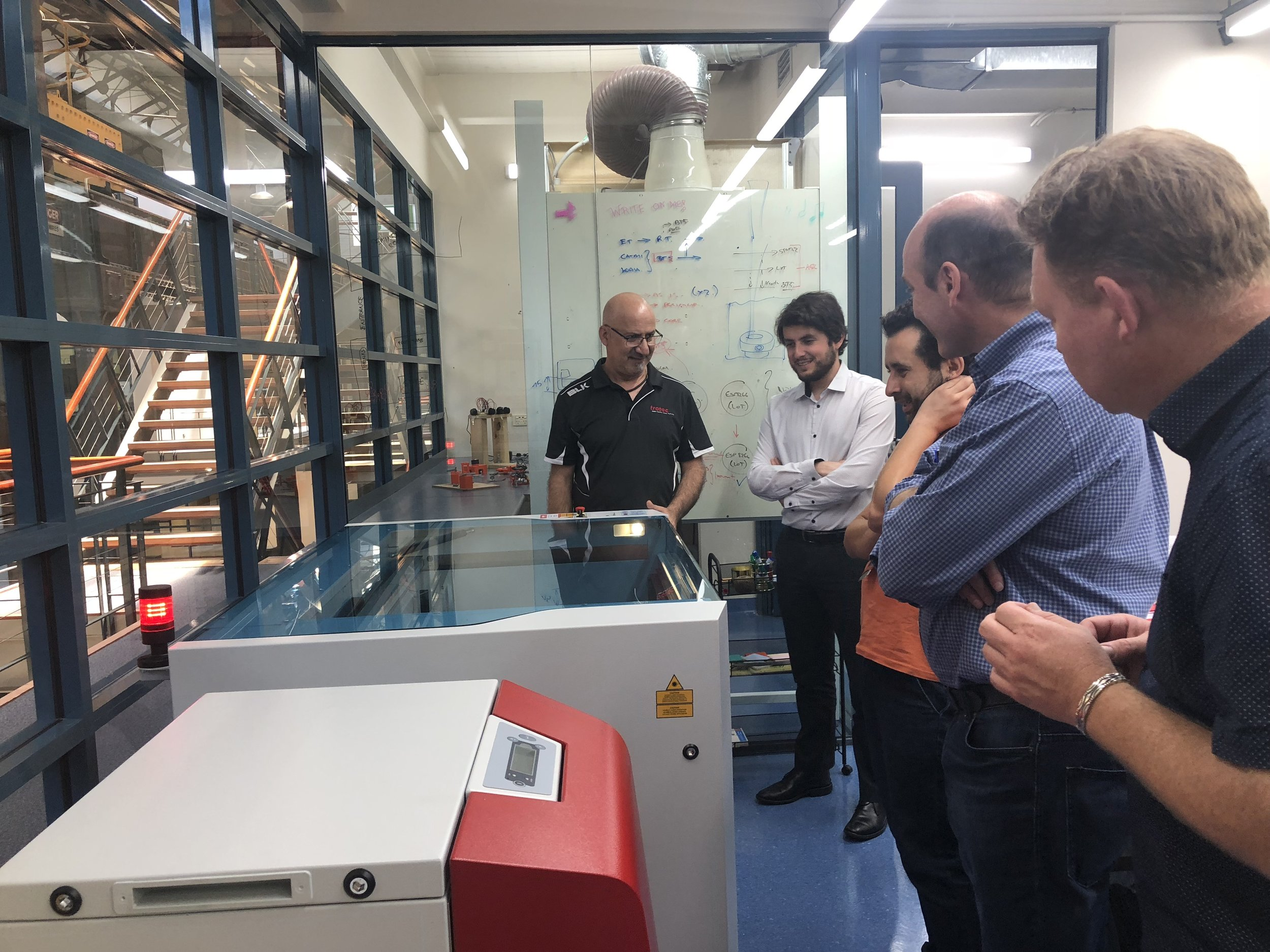 A group of people standing around the laser cutter