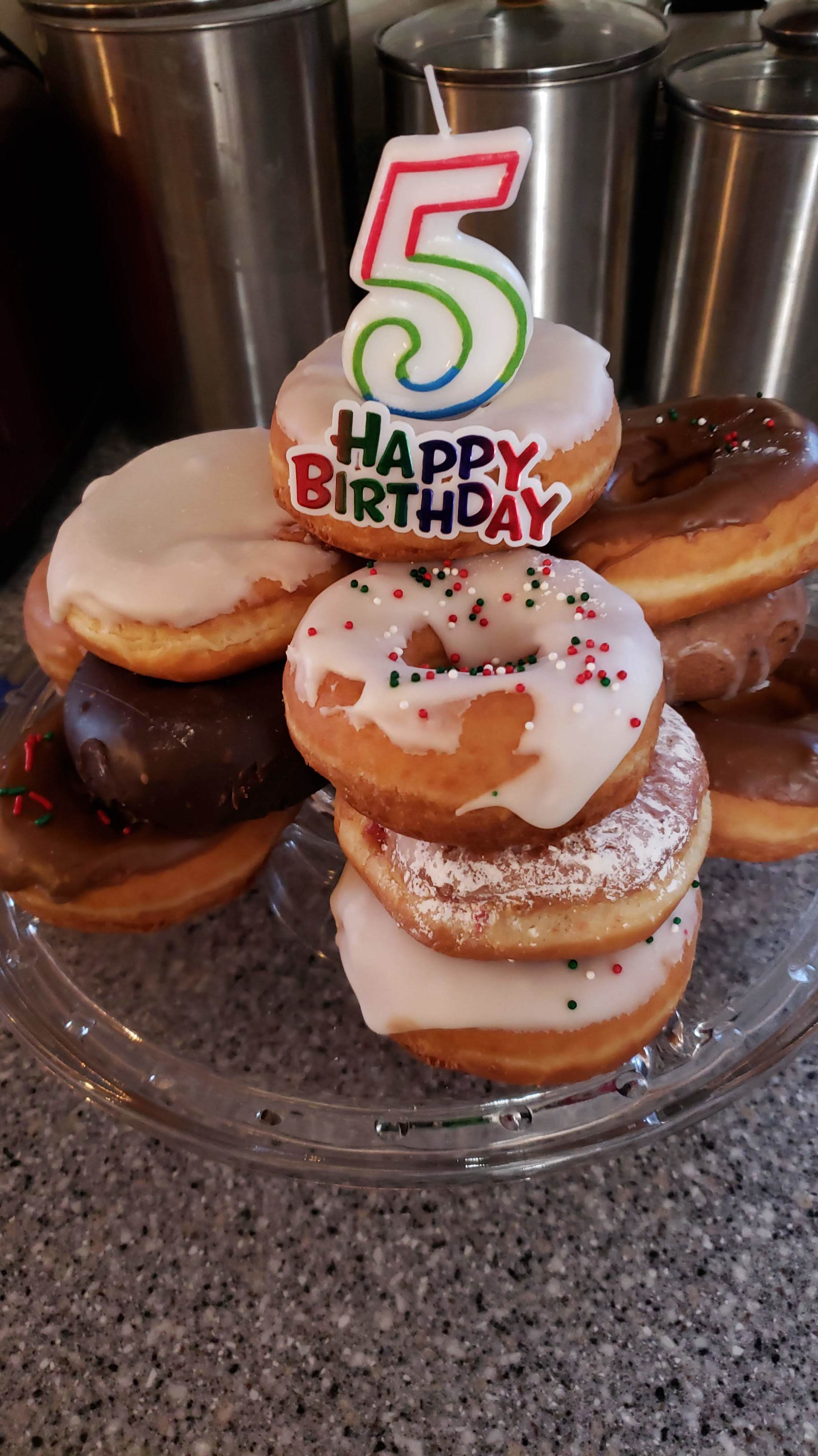 When you attend a birthday party at our house, I can guarantee it will have a doughnut cake, because they are super easy to put together, incredibly inexpensive to make (we have done Krispy Kremes before, but went with Safeway and Walmart this time around), and give your guests some options.